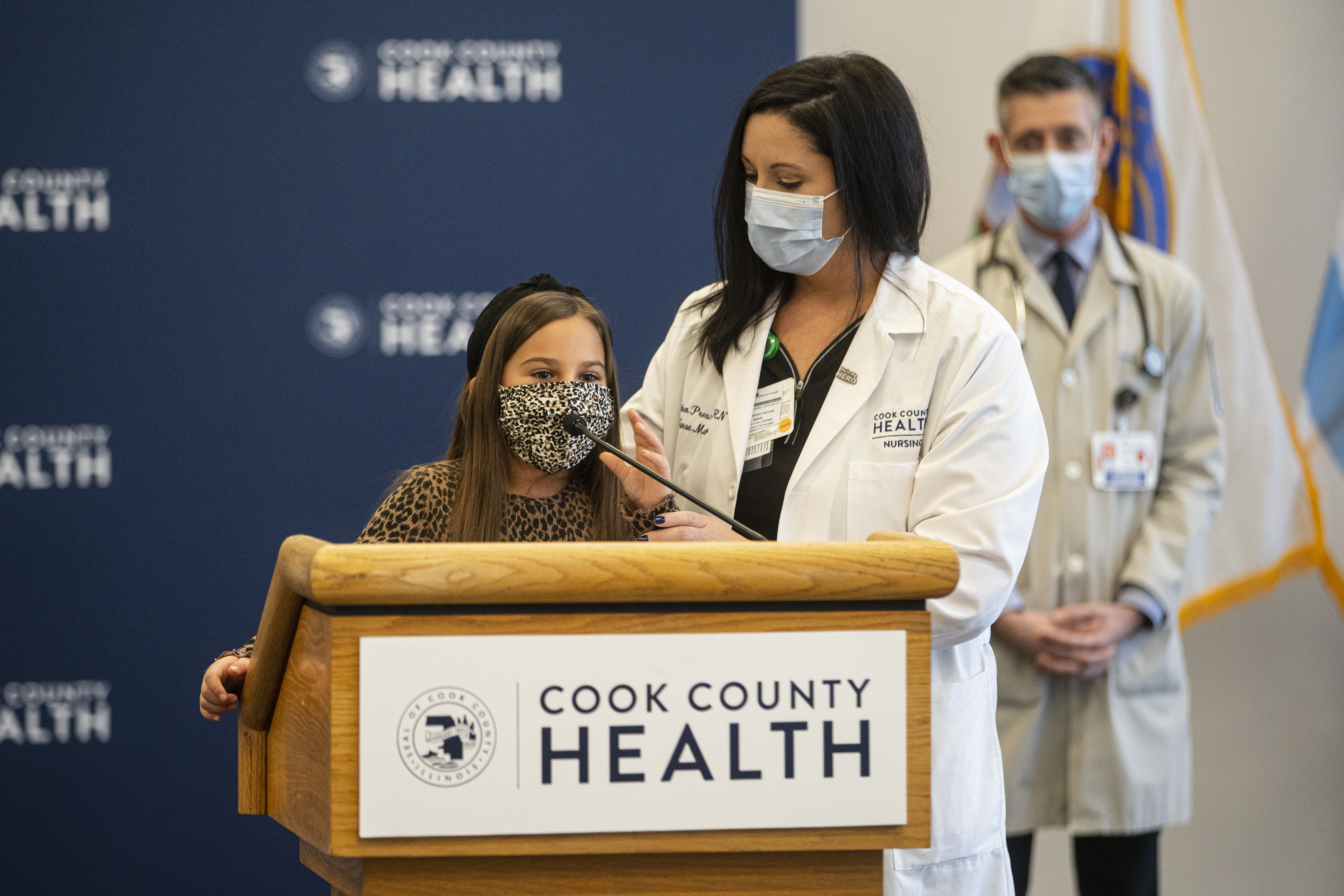 Mia Lopez, 7, speaks at a news conference Monday, Nov. 23, 2020 organized by Cook County Health. With her is her mom, Heather Prescaro, an emergency department nurse. They and other Cook County Health staff are asking residents to stay at home for Thanksgiving to limit the spread of the coronavirus.