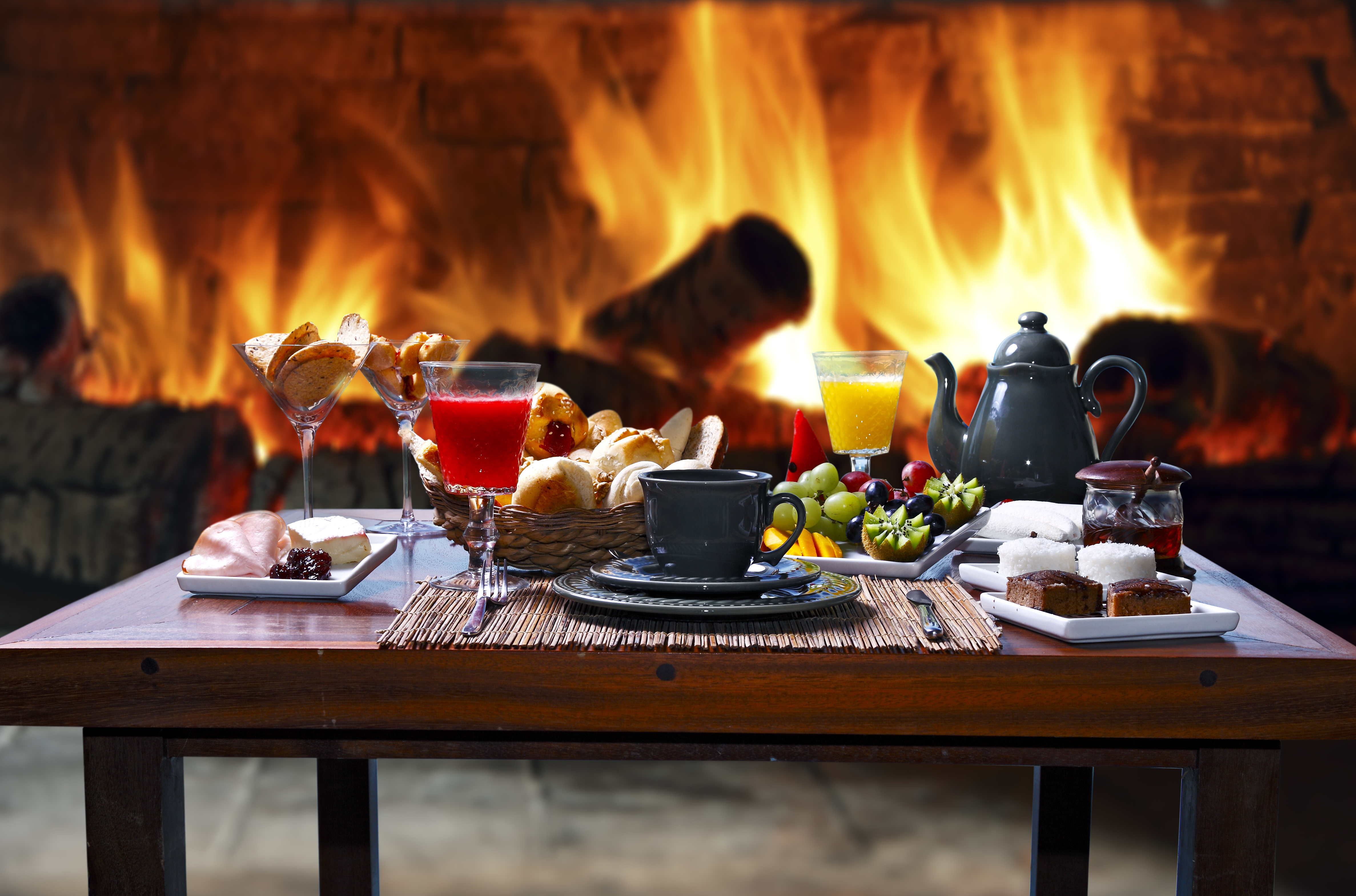 A table in front of a fireplace laden with food and drinks, including a tea pot, fruit plate, and bread basket