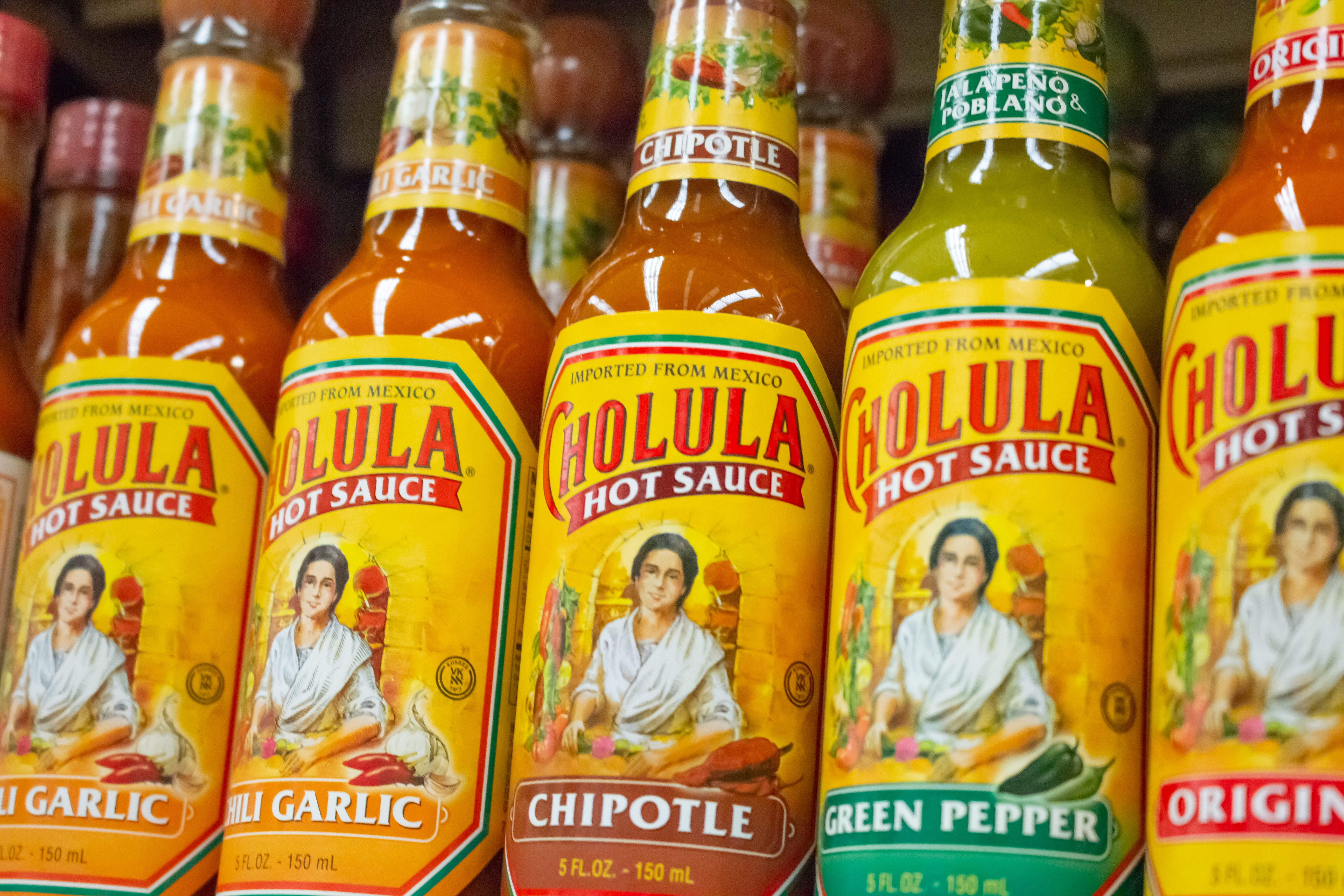 Bottles of Cholula hot sauces lined up on a grocery store shelf.