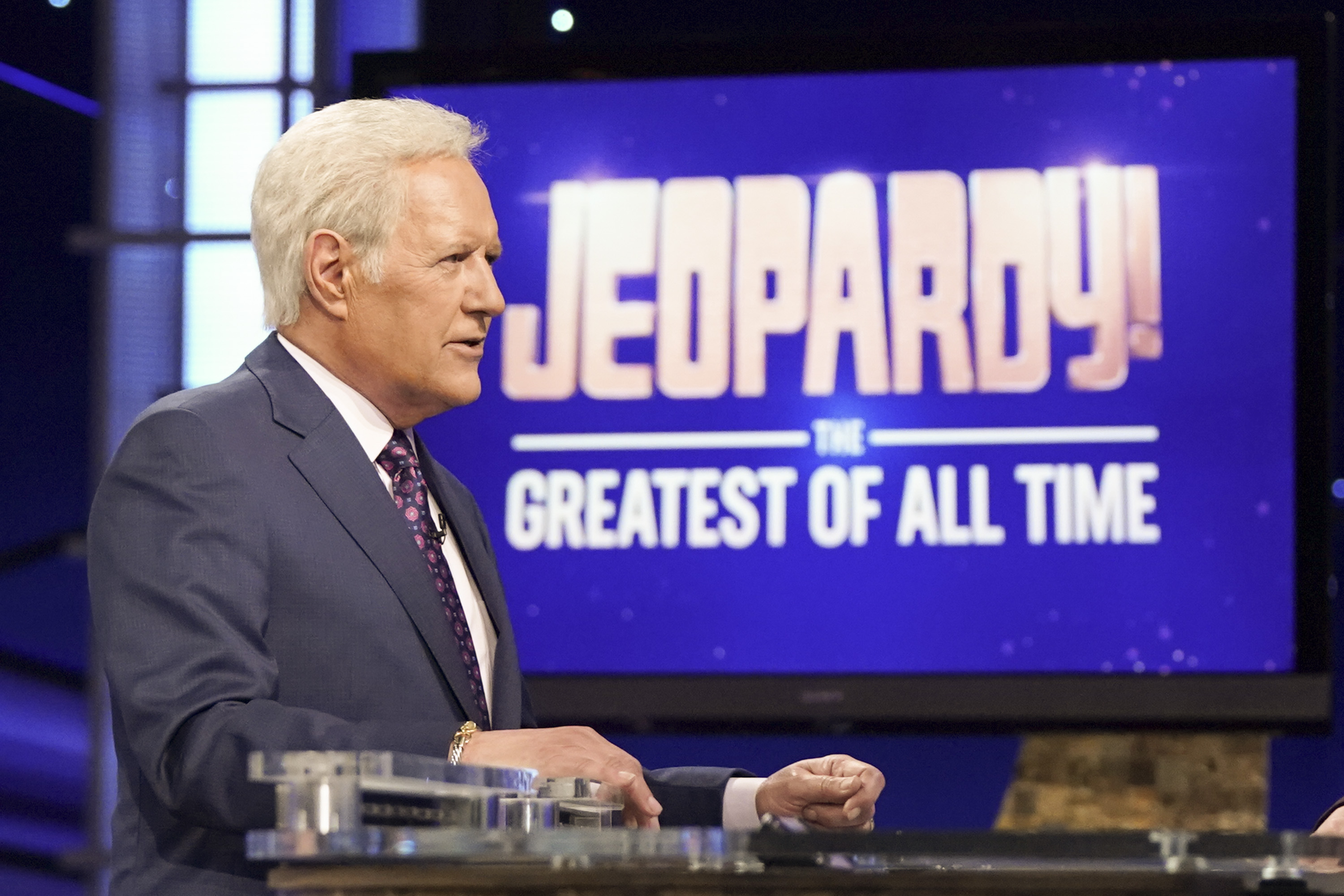 """In a dark grey suit, white button-down, and red tie, a white-haired Alex Trebek stands in front of a screen reading """"Jeopardy! The Greatest of All Time."""""""