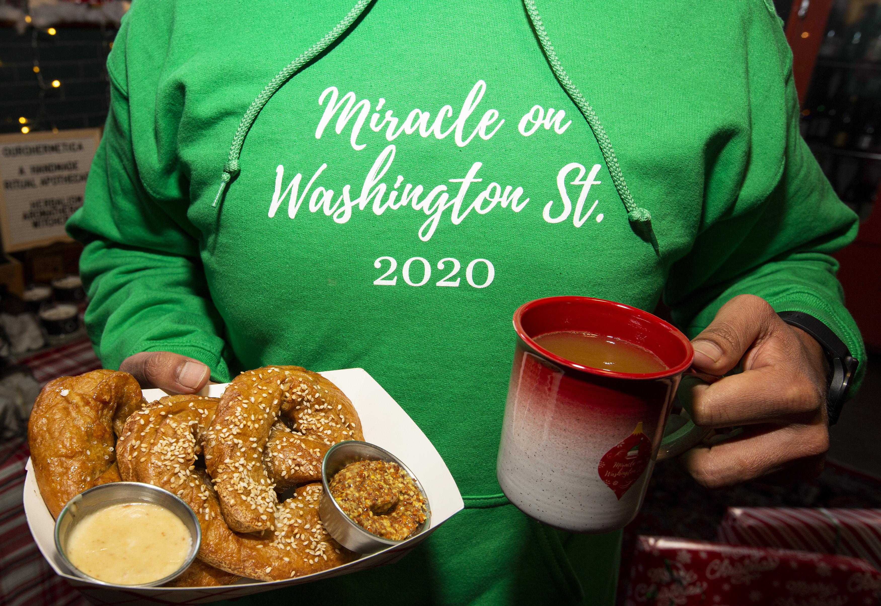 """A person in a green hoodie that reads """"Miracle on Washington St. 2020"""" holds a paper plate with a big, soft pretzel and a mug of something hot."""