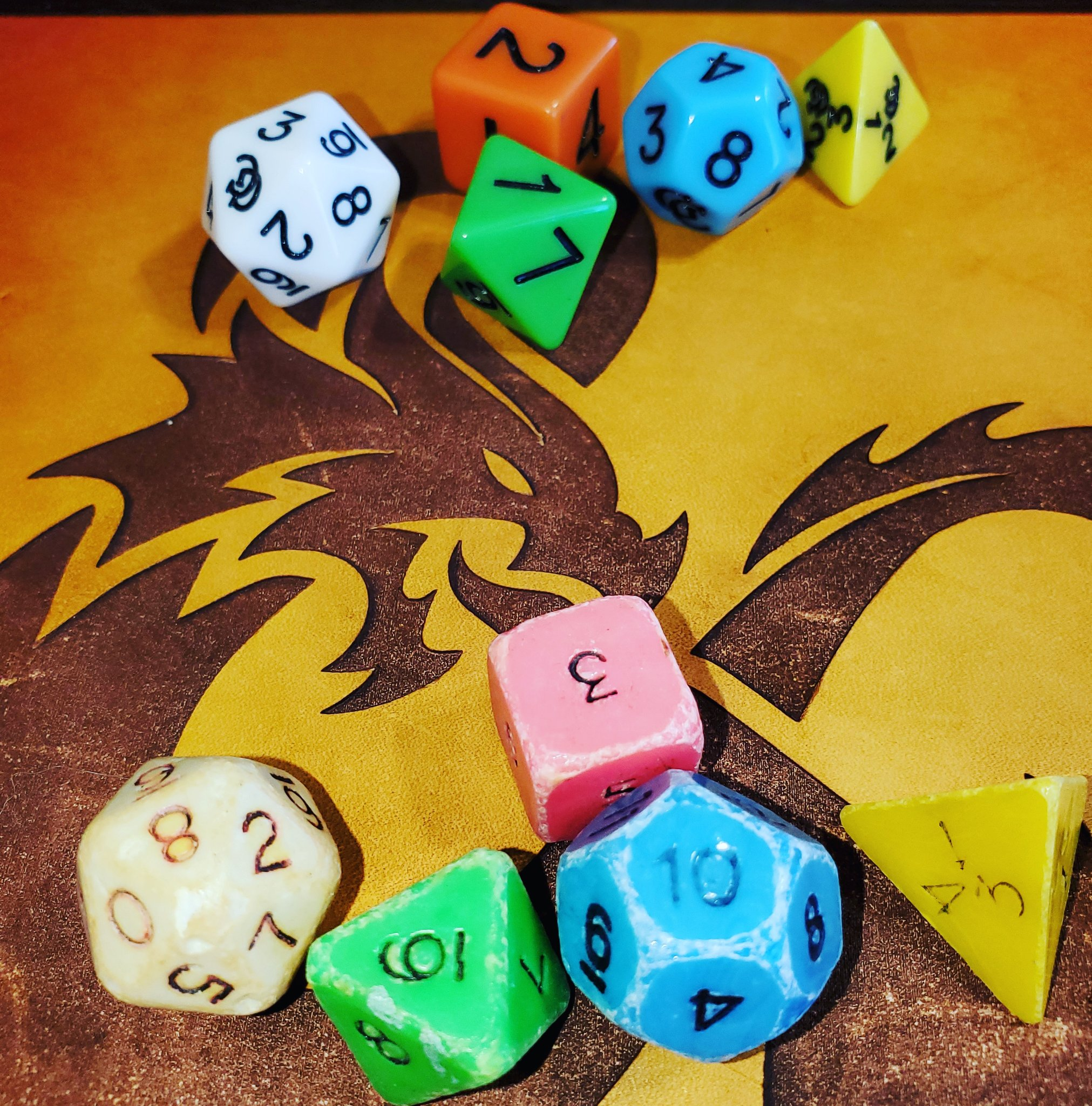 a set of colorful Dungeons & Dragons dice on a table with a dragon on it