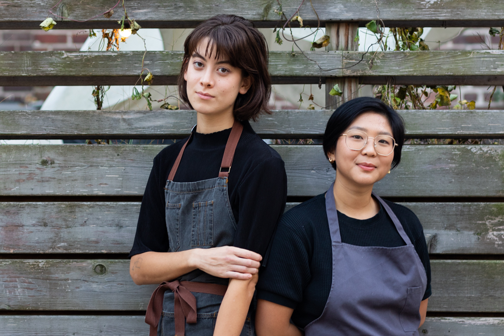 Two people wearing black shirts and blue aprons standing against a grey fence