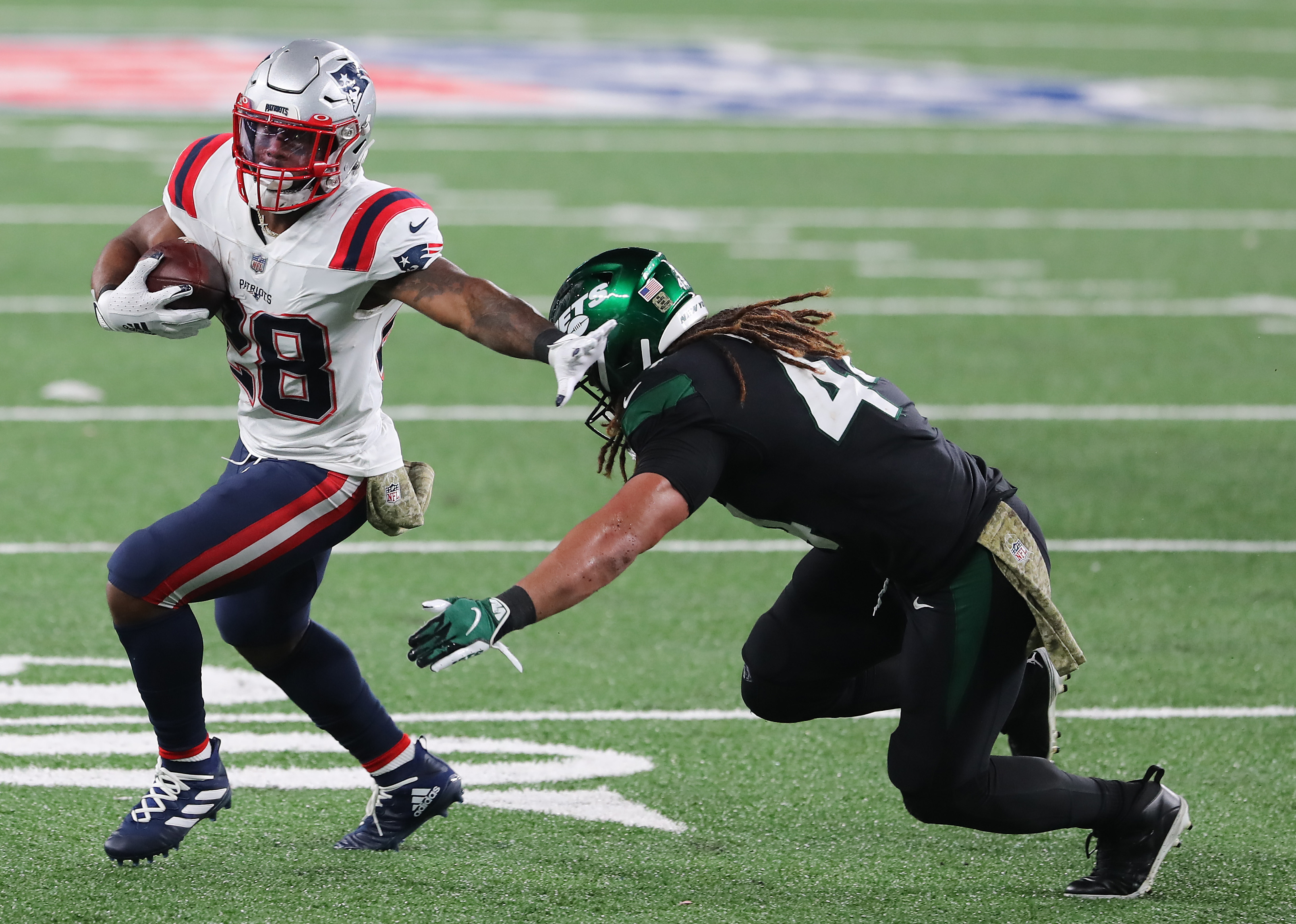 James White #28 of the New England Patriots carries the ball as Harvey Langi #44 of the New York Jets defends during the second half at MetLife Stadium on November 09, 2020 in East Rutherford, New Jersey