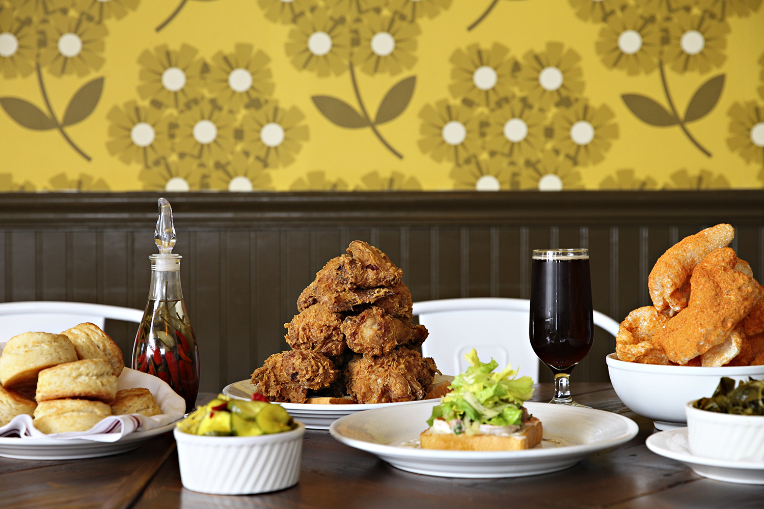 A long table inside Revival's Minneapolis location is set with two towers of fried chicken and a host of sides