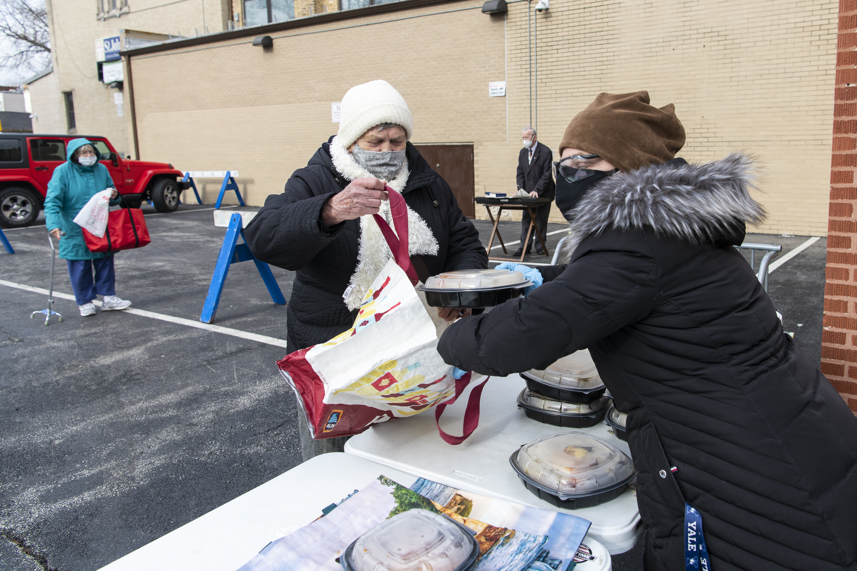 A volunteer with the Joined Hands Food Pantry on the Northwest Side hands out a Thanksgiving meal Thursday.