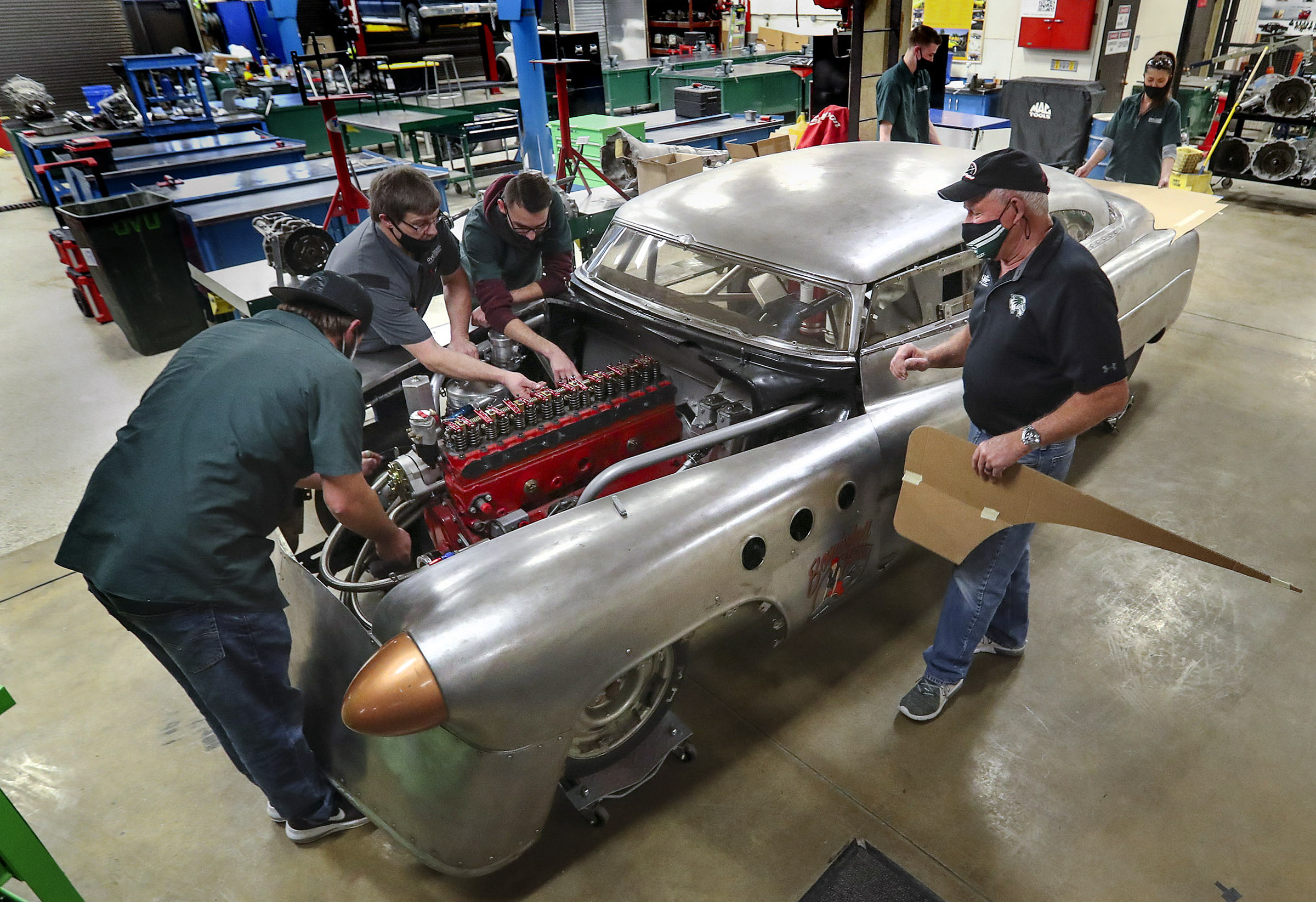 "Jeff Holm, UVU Transportation Technology professional in residence, right, and Todd Low, UVU race team director, second from left, work with UVU automotive students Jordan Olsen, left, Anderson Workman, James Spackman and Hadley Tibbitts, right, as they work on ""Bombshell Betty,"" the iconic 1952 Buick that broke six land speed world records at the Bonneville Speedway in Utah, at the Sparks Automotive building on the UVU campus in Orem on Wednesday, Nov. 18, 2020. The team has updated and reengineered the vehicle to break the 200 mph mark."
