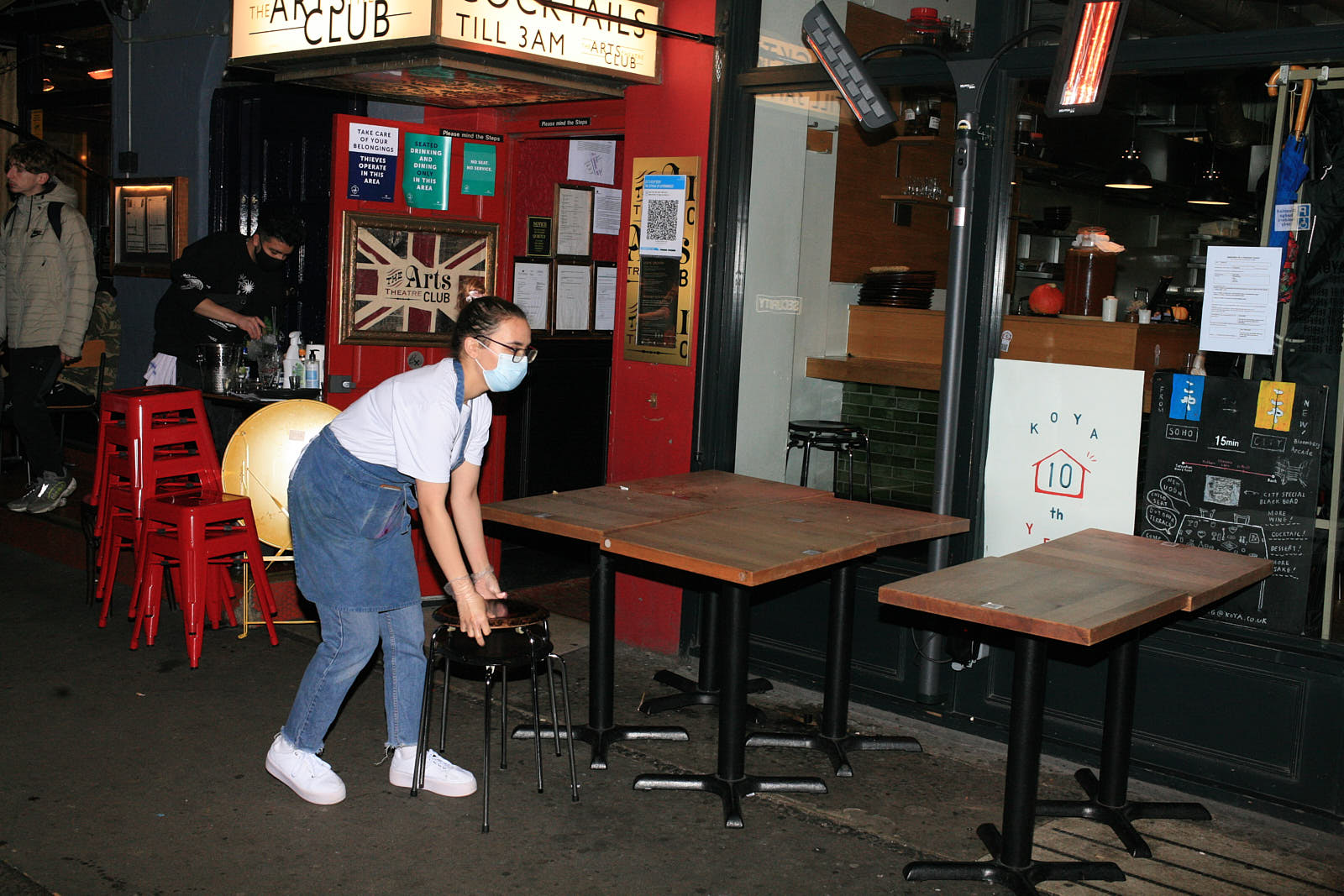 A staff member in a mask moves tables outside Koya restaurant in Soho