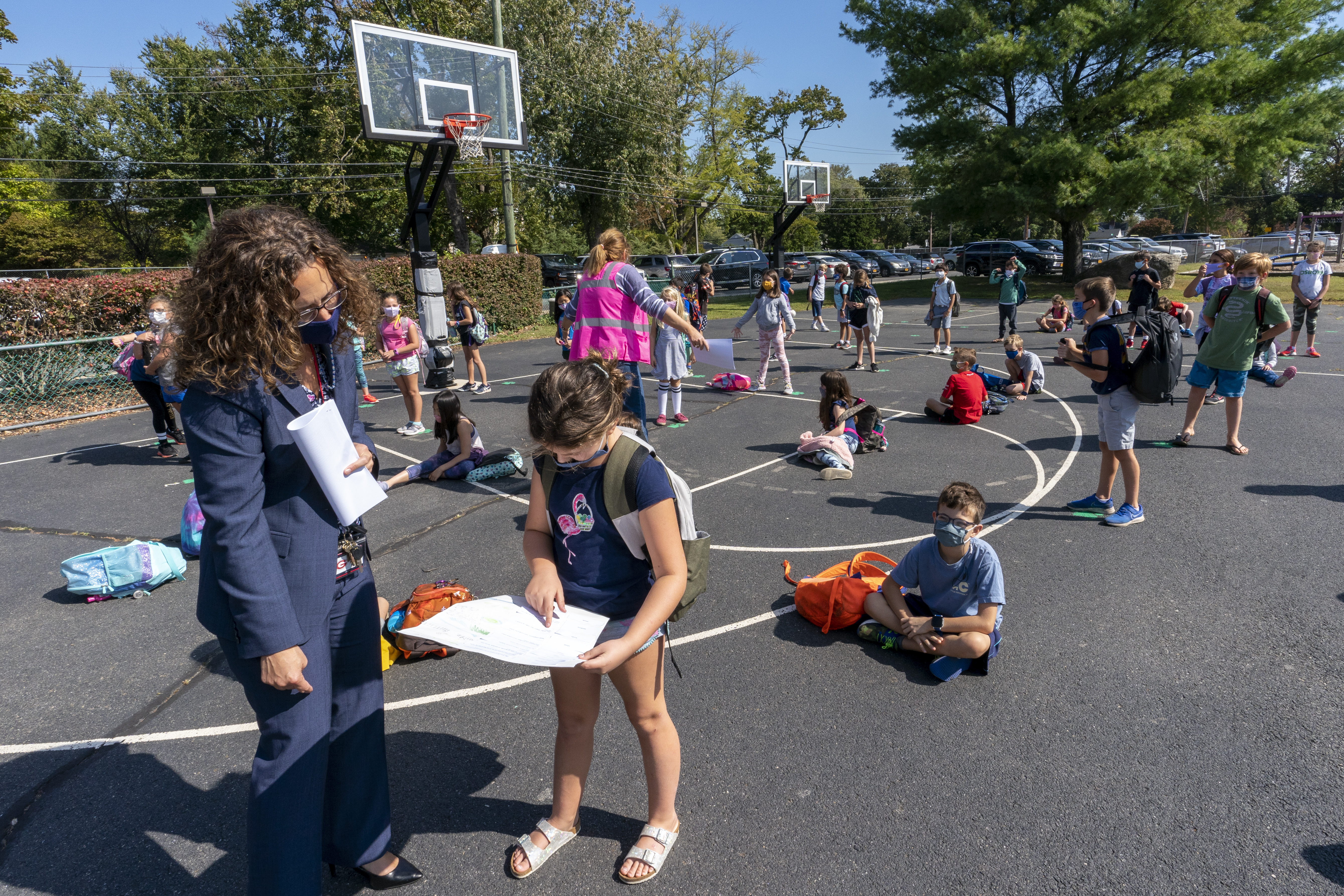 Principle Angela Garcia looks over a student's homework as children line up before entering the Osborn School, Tuesday, Oct. 6, 2020, in Rye, N.Y.
