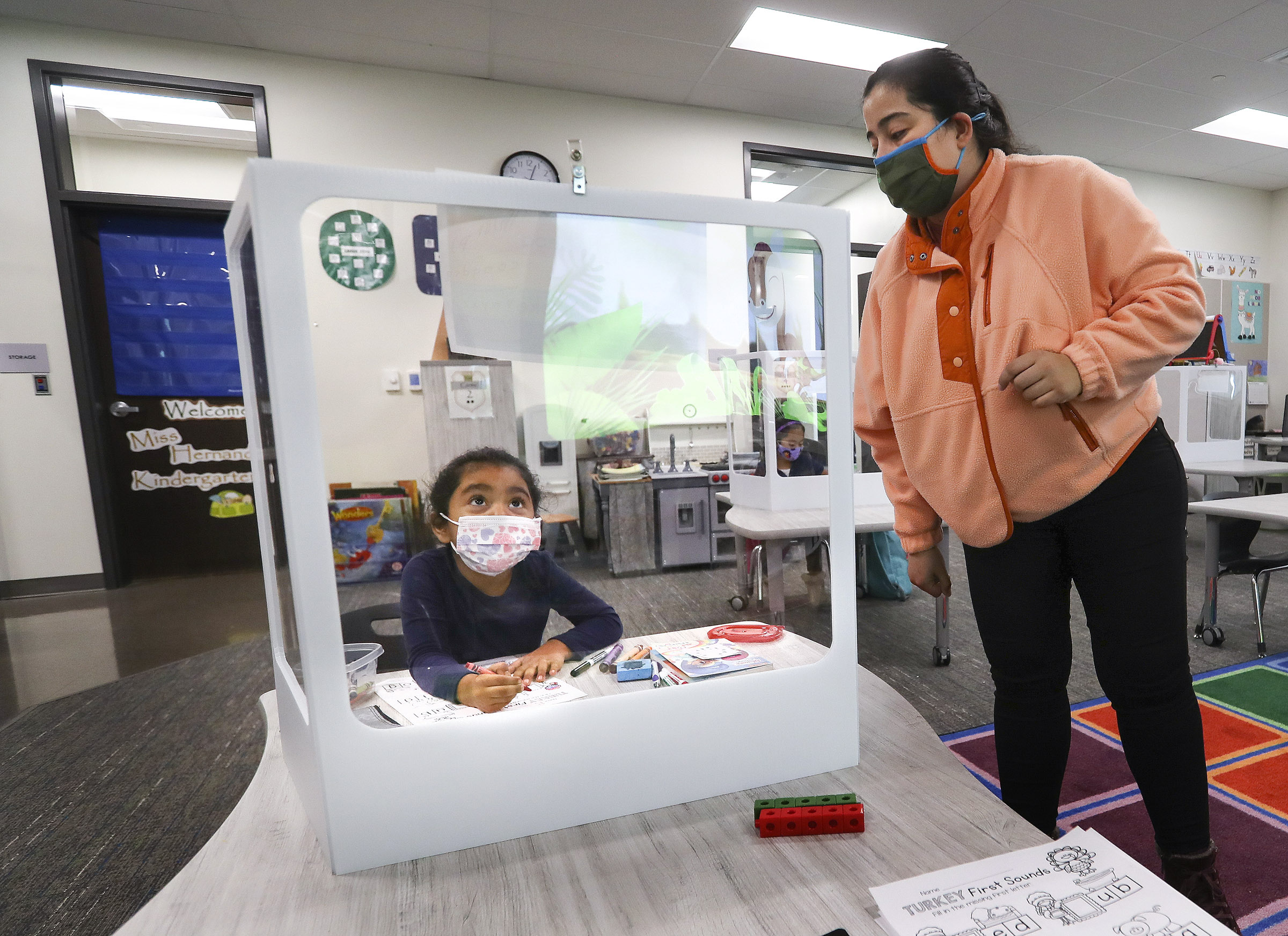 Edison Elementary School kindergartener Rebeca Prado sits behind a protective screen as she works on English skills with her teacher Veronica Hernandez at the school in Salt Lake City on Monday, Nov. 23, 2020.