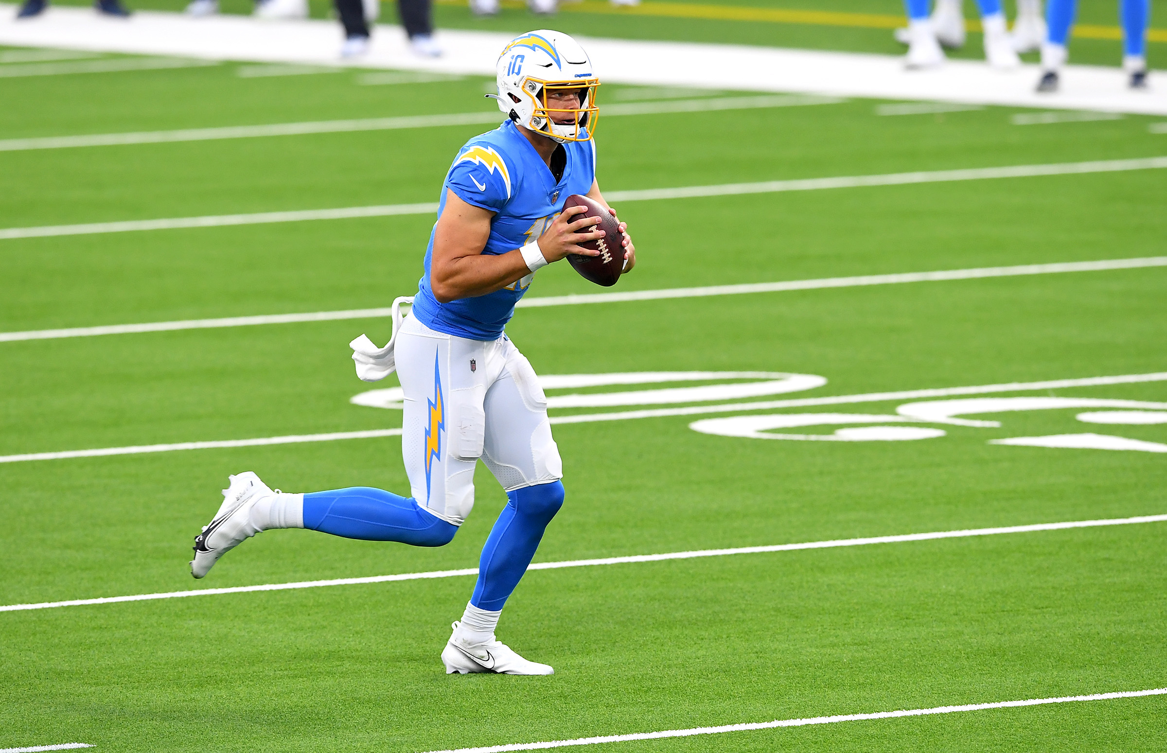 Los Angeles Chargers quarterback Justin Herbert (10) rolls out to throw a touchdown pass to wide receiver Keenan Allen (not pictured) against the New York Jets in the second half at SoFi Stadium.