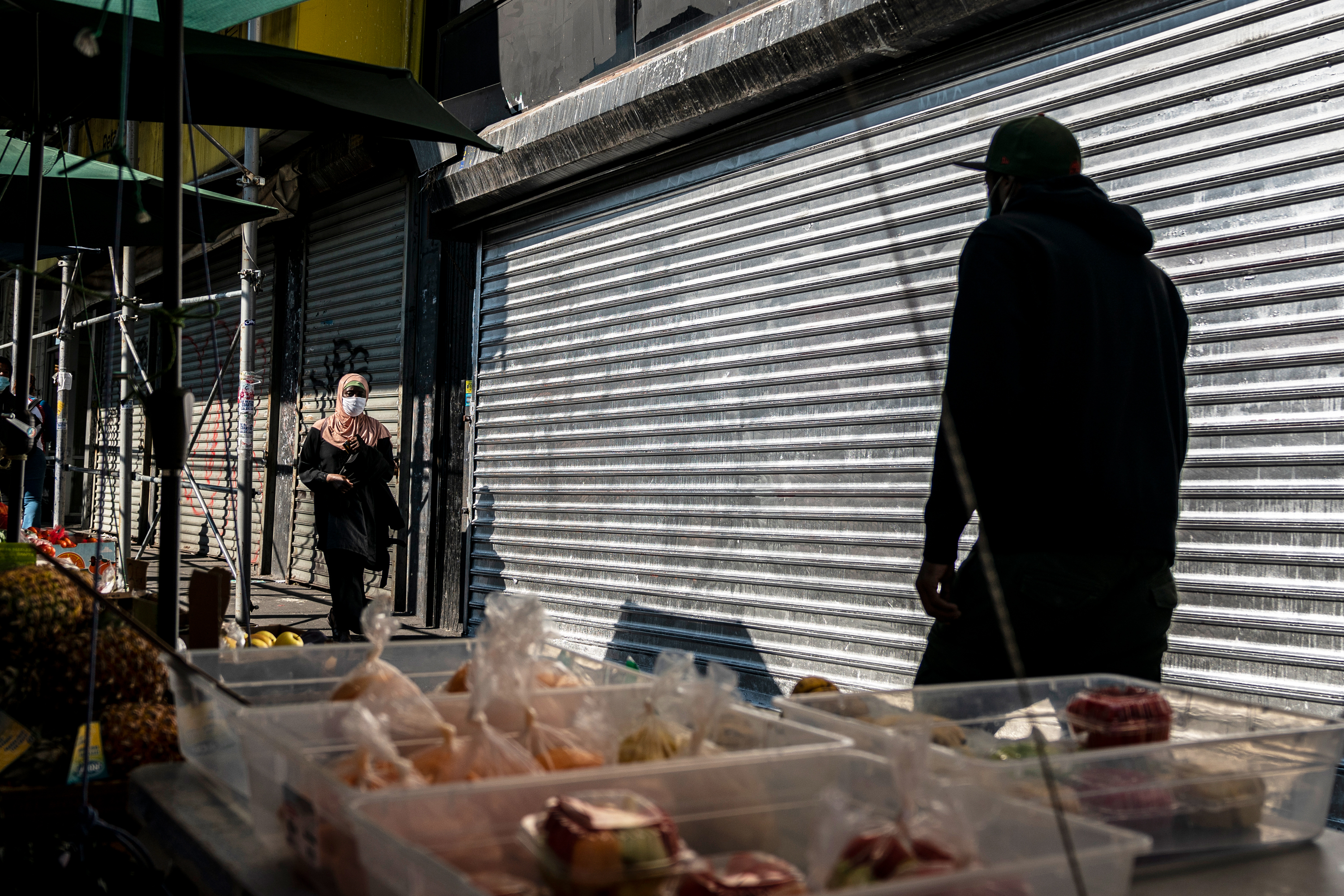 People walk by shuttered storefronts at The Hub in the South Bronx Oct. 9, 2020.
