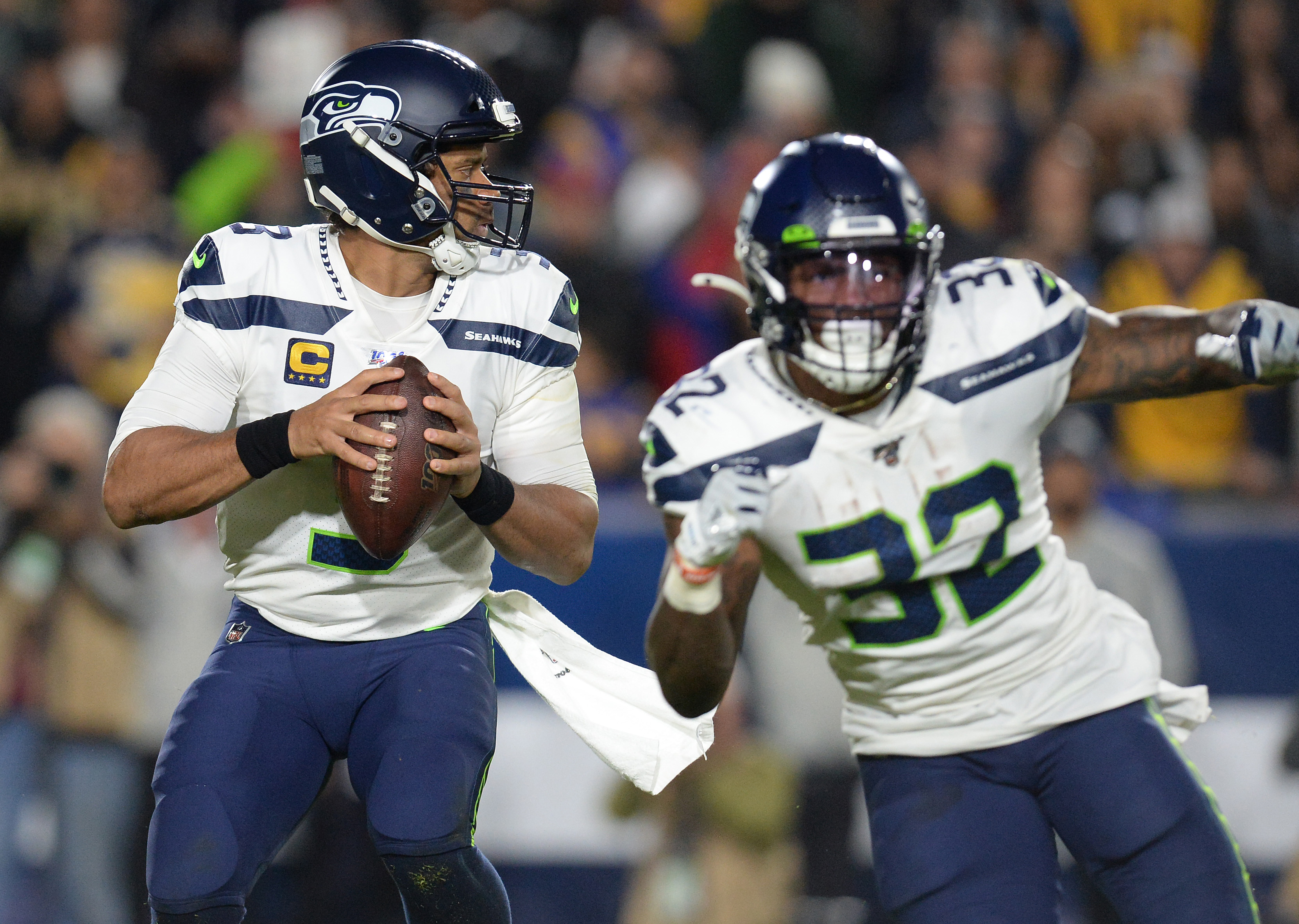 Seattle Seahawks quarterback Russell Wilson drops back to pass as running back Chris Carson provides coverage against the Los Angeles Rams during the second half at the Los Angeles Memorial Coliseum.