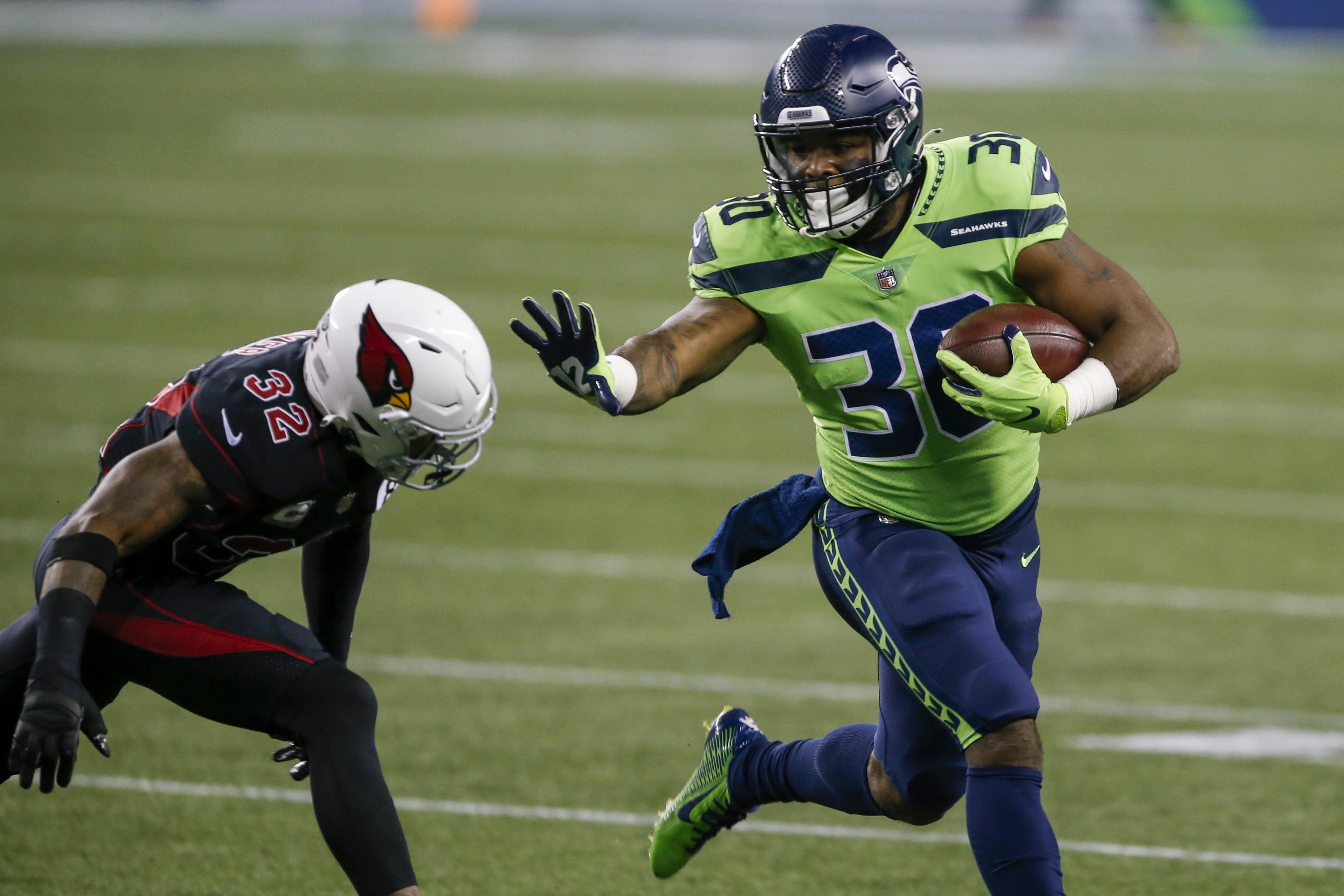 Seattle Seahawks running back Carlos Hyde runs the ball against Arizona Cardinals safety Budda Baker (32) during the first quarter at Lumen Field.