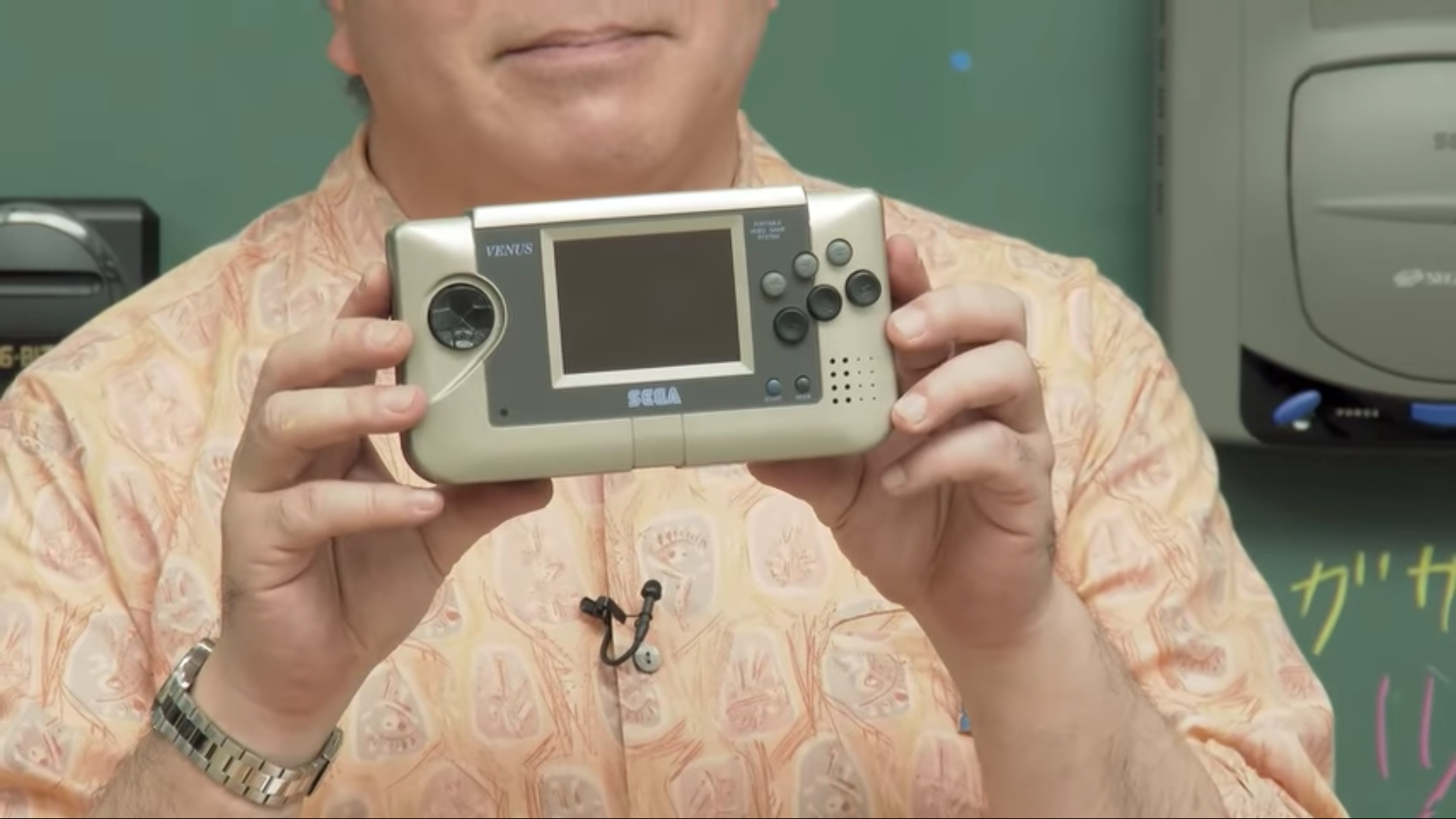 Close up of Hiroyuki Miyazaki's hands holding the Sega Venus handheld prototype