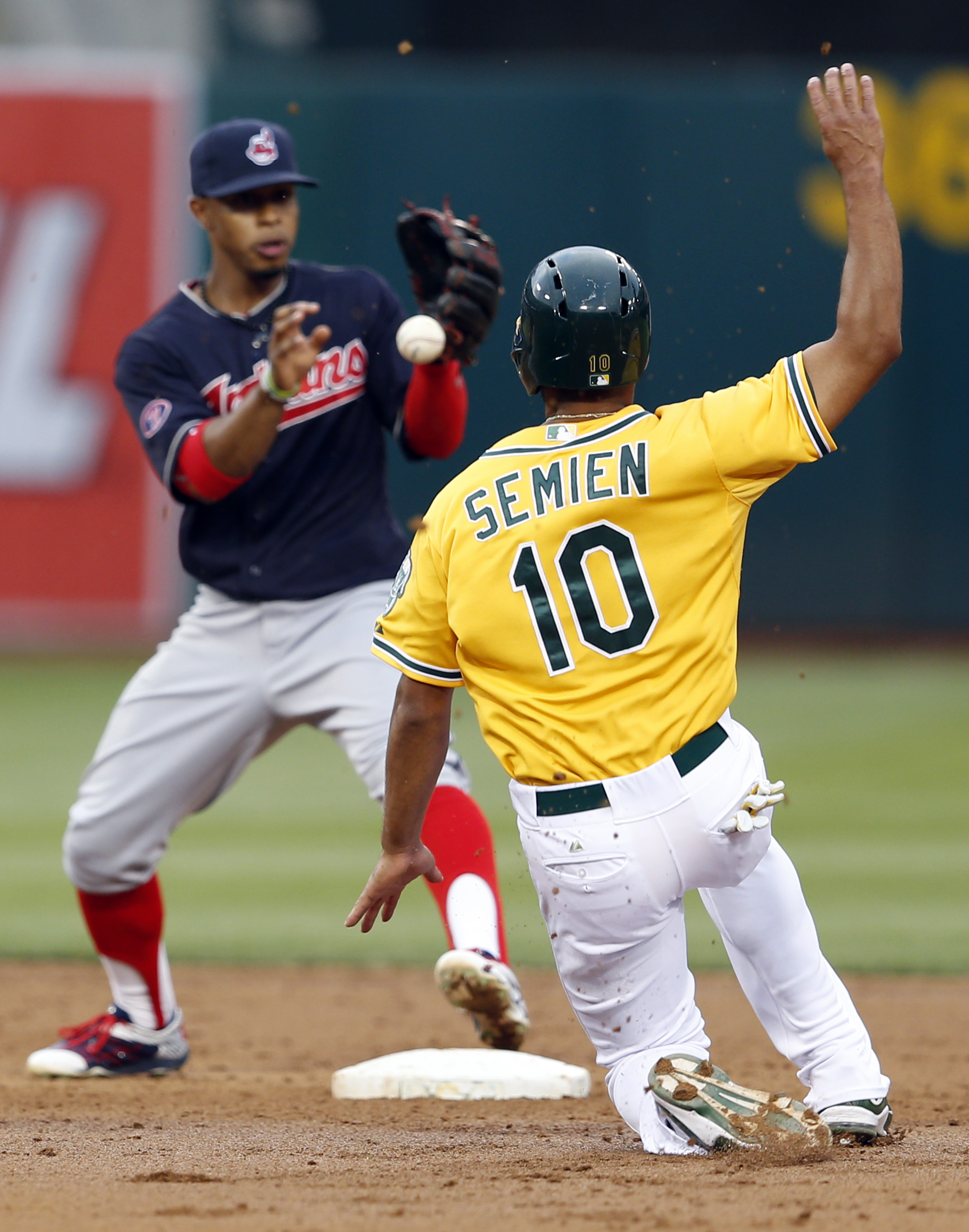 Cleveland Indians' Francisco Lindor (12) forces Oakland Athletics' Marcus Semien (10) out as he breaks up a double play attempt in the third inning of a MLB game at O.co Coliseum in Oakland, Calif., on Friday, July 31, 2015. (Ray Chavez/Bay Area News Grou