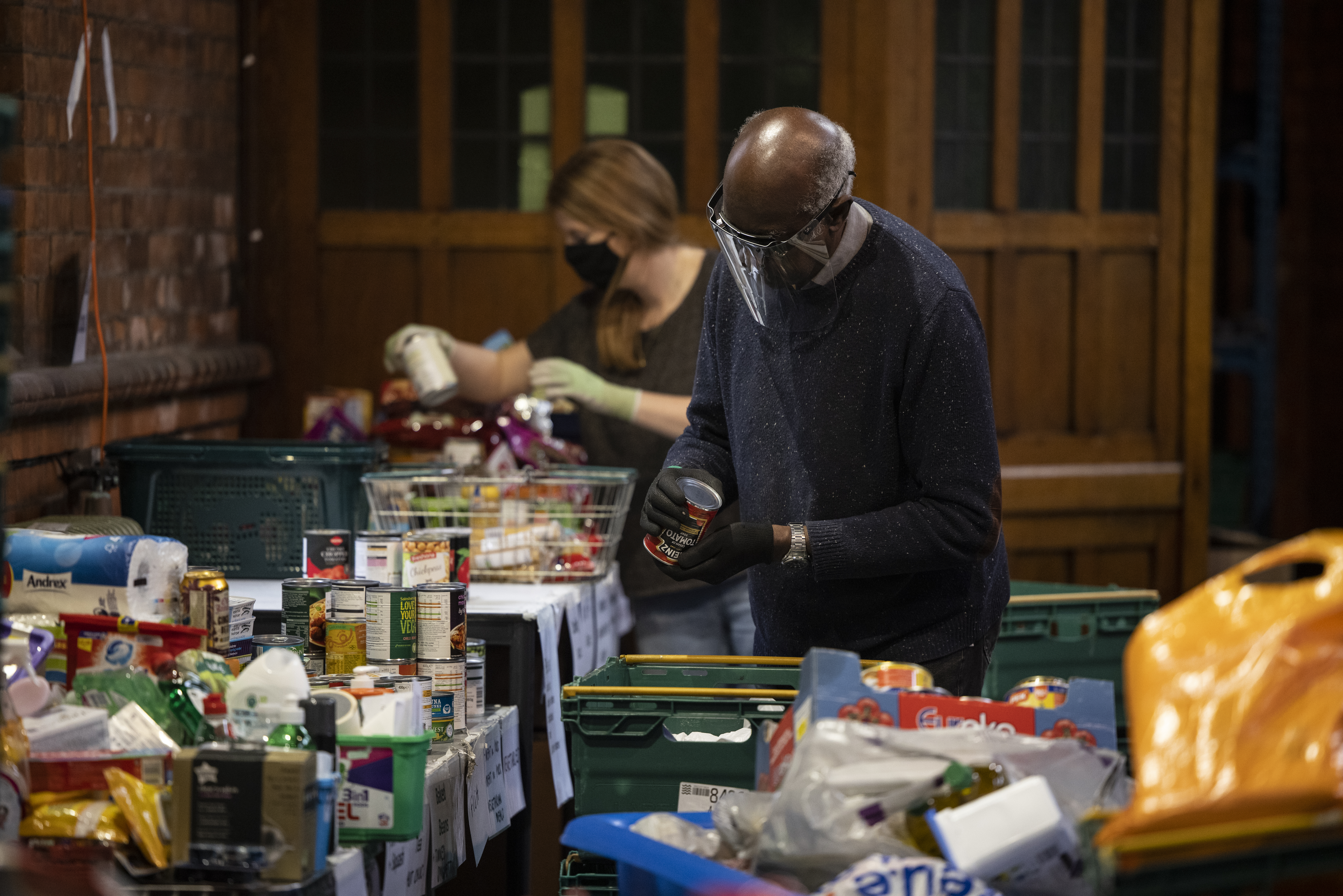 Trussell Trust volunteers stand over crates of food, packing food parcels for London food banks