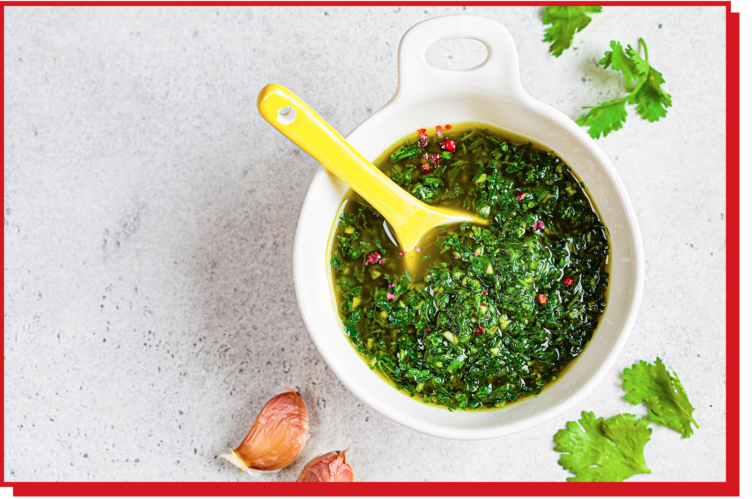 Finely chopped green herbs in olive oil in a ramekin with ceramic spoon.