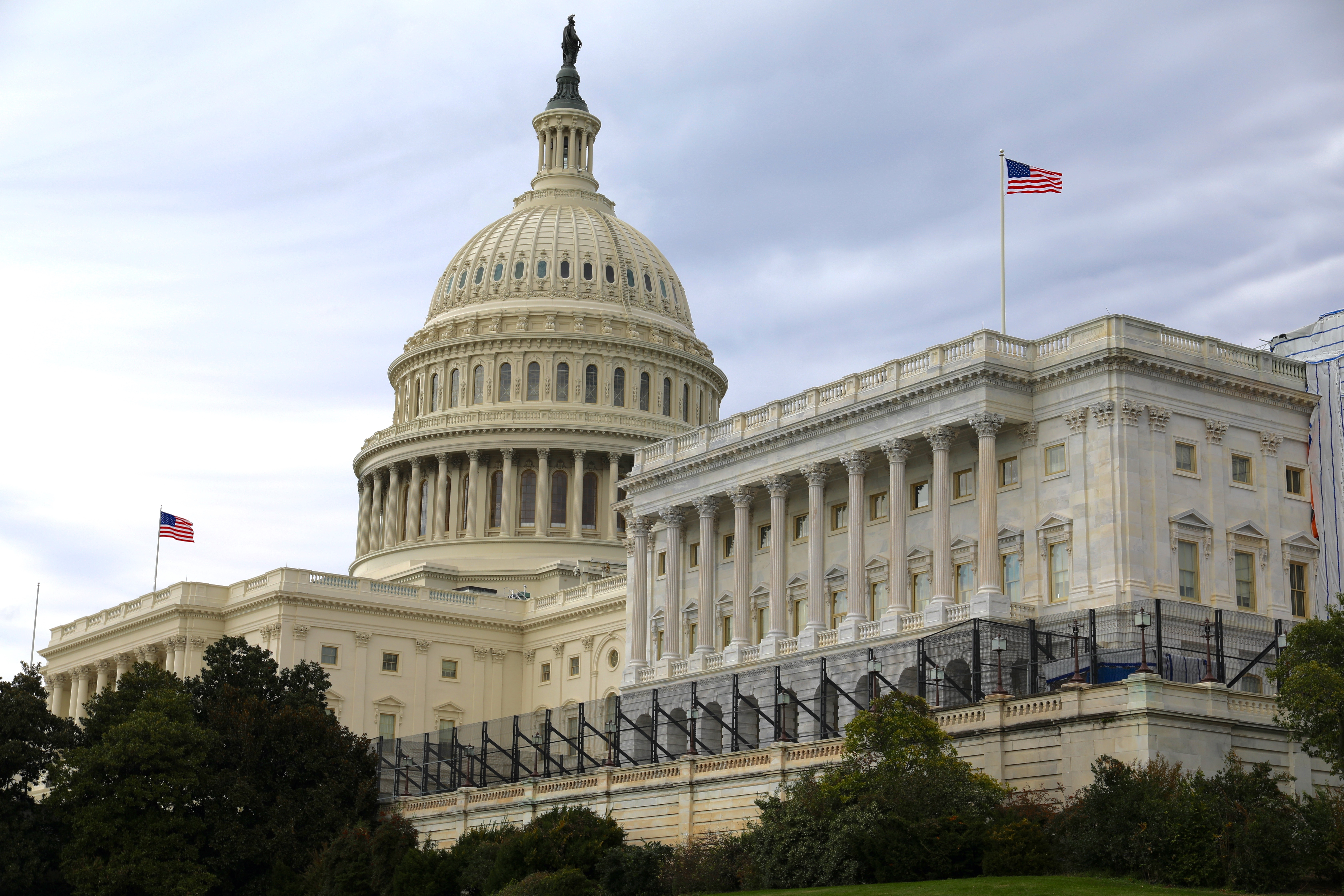 The exterior of the US capitol building photographed from a low angle on a partially cloudy day.