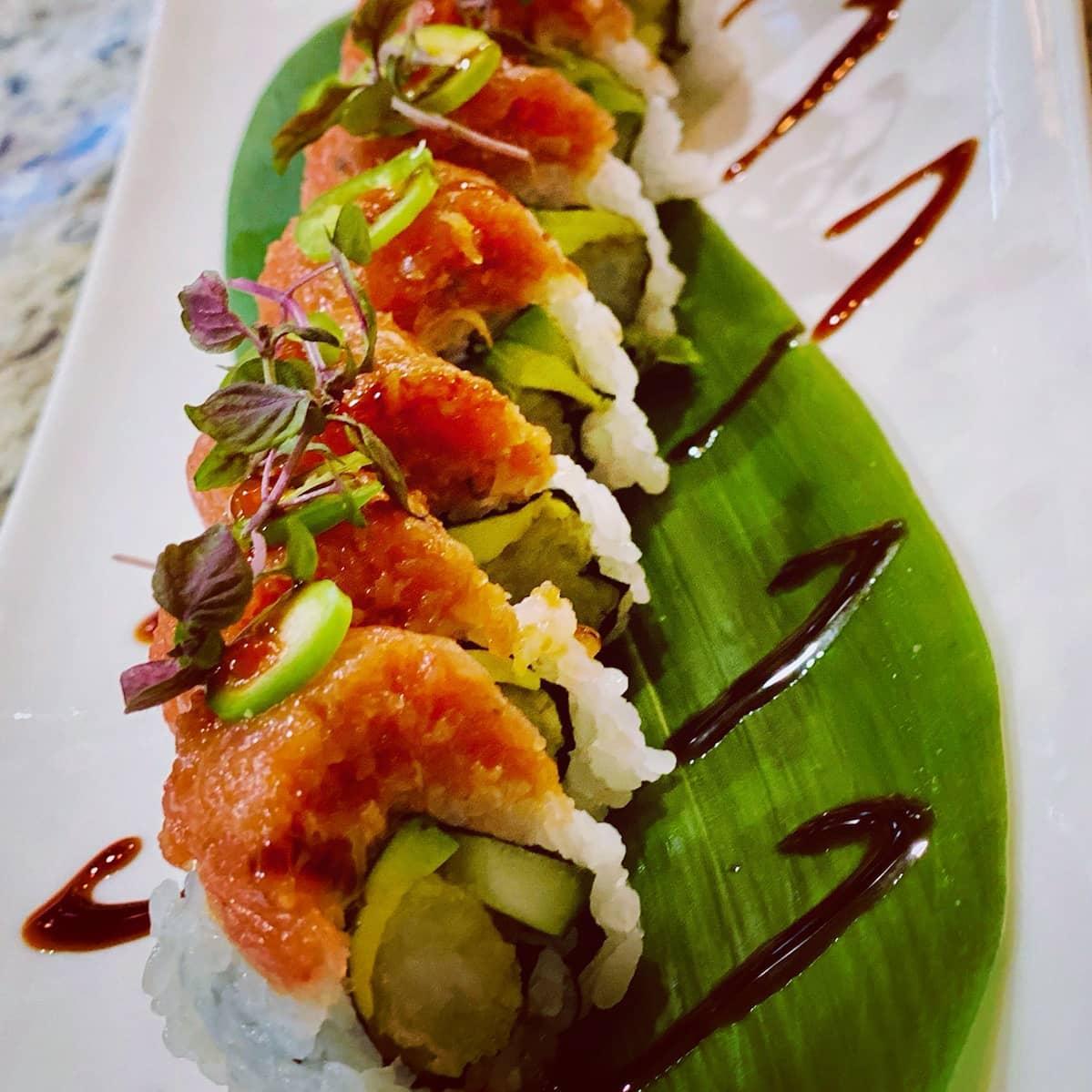 A sushi roll on a banana leaf