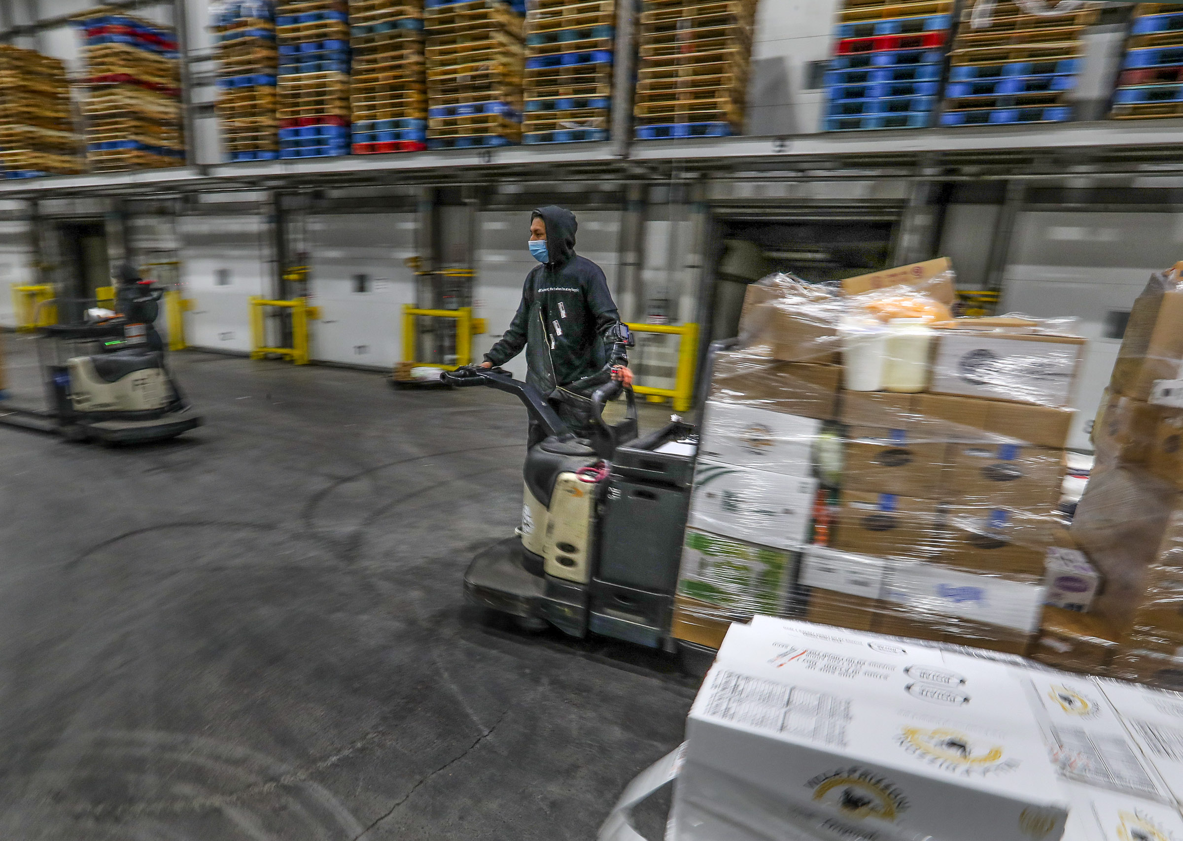 Saul Flores, a loader for Nicholas and Company, uses a forklift to load cold food into refrigerated trucks at the company's warehouse in Salt Lake City on Tuesday, Dec. 1, 2020.