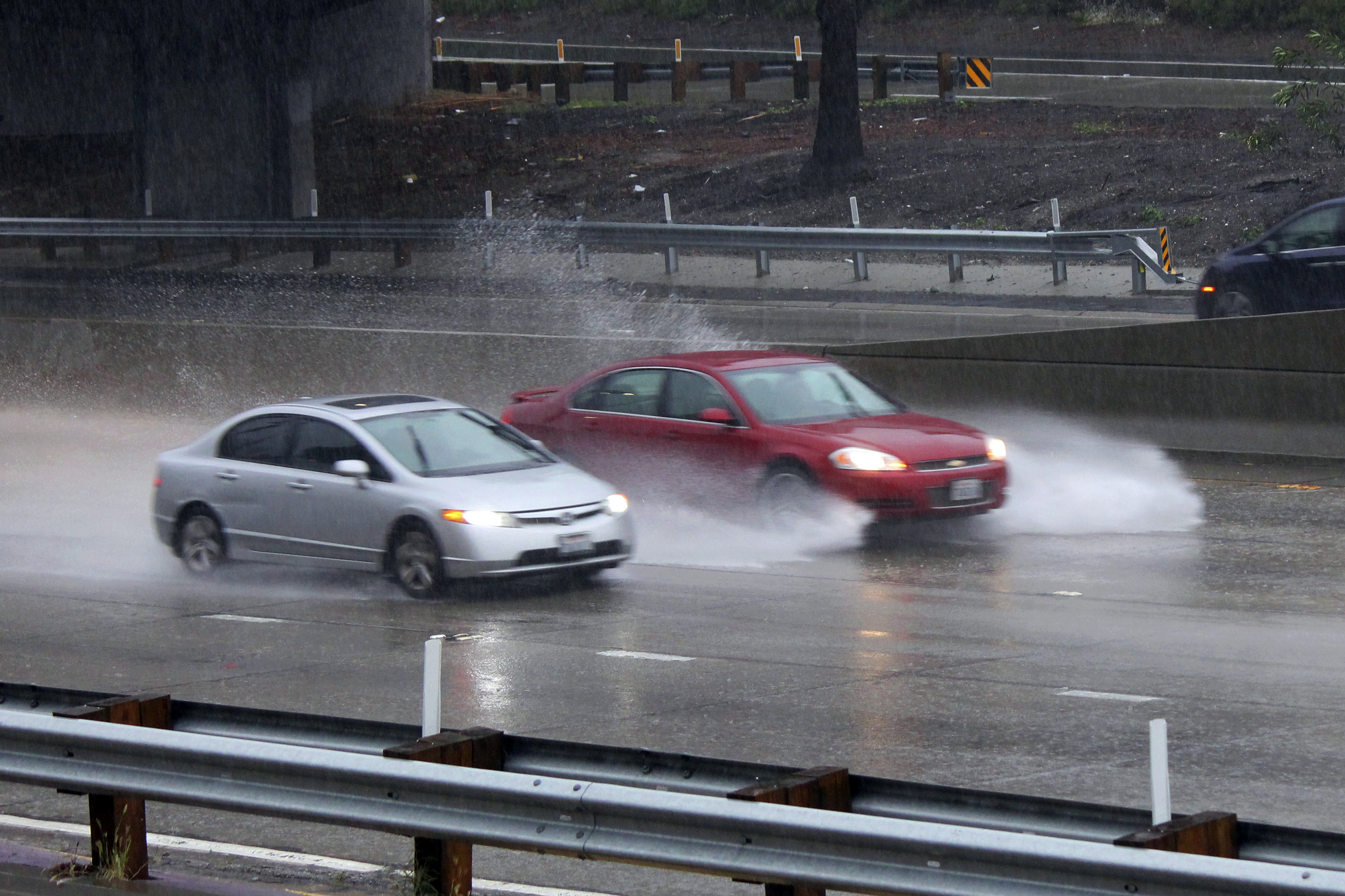 Cars on the northbound Harbor Freeway (I-110) in downtown Los Angeles plow through deep water during a torrential downpour Monday, April 6, 2020.