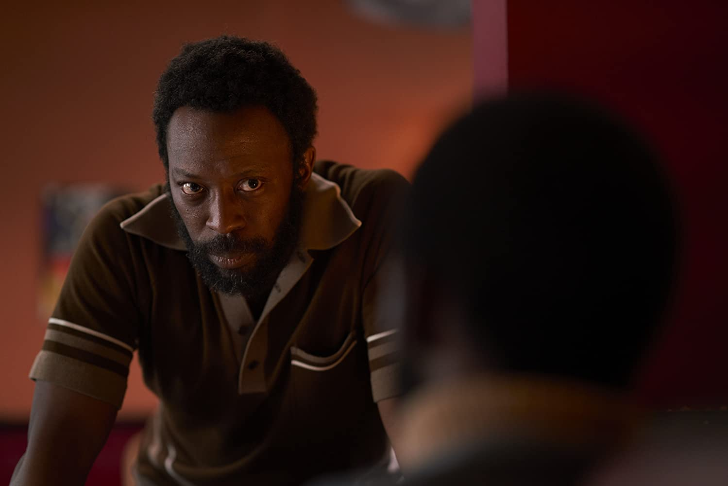 In a red-painted room, a bearded man wearing a brown polo shirt assumes a serious facial expression while leaning forward on a table and listening to another person who is obscured in the foreground.