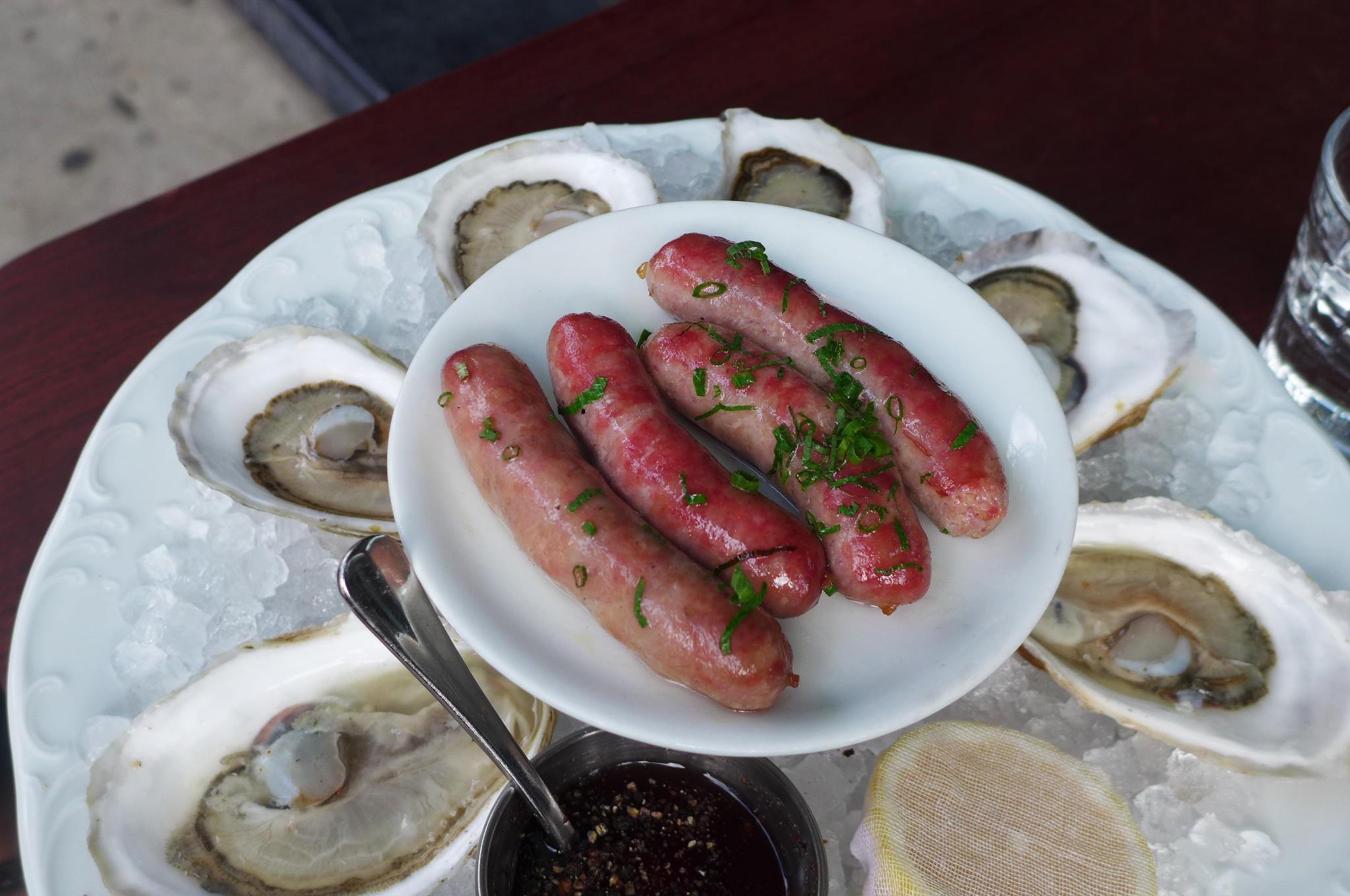 A tray of six raw oysters on ice with a small plate of sausages balanced on top.