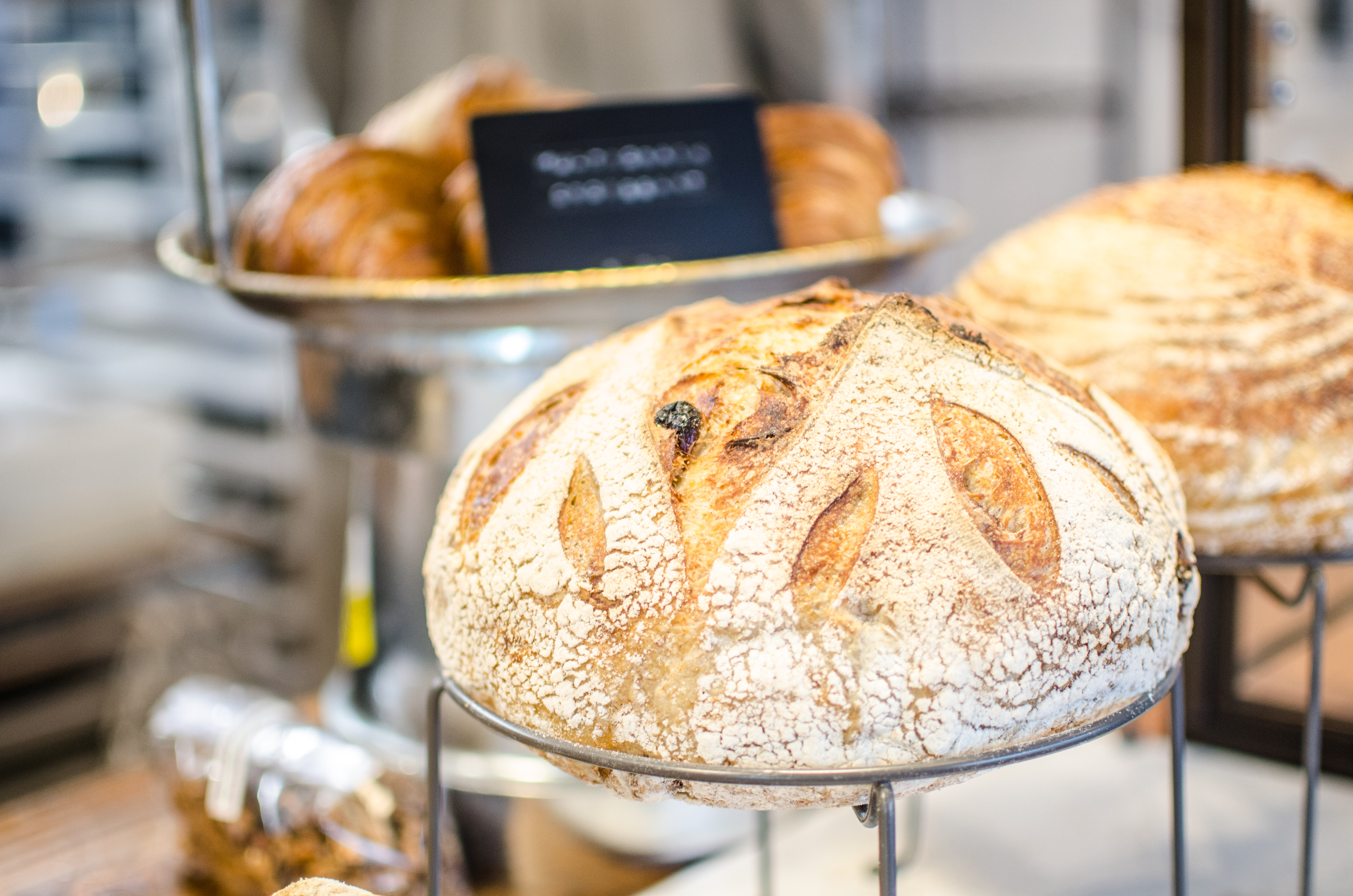 Sourdough loaves sit on display in a bakery, with croissants visible in the background