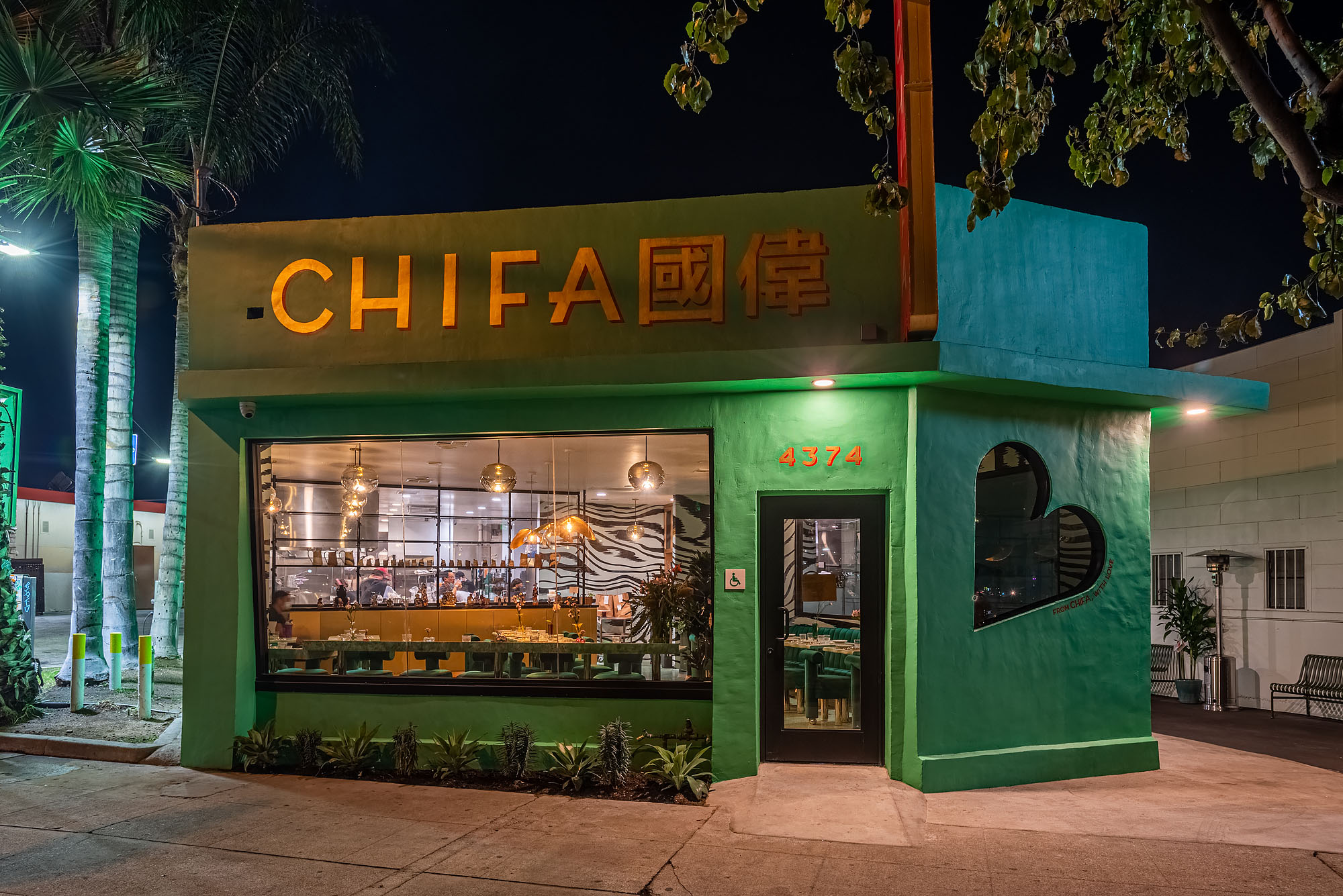 A restaurant painted green at nighttime in Los Angeles.