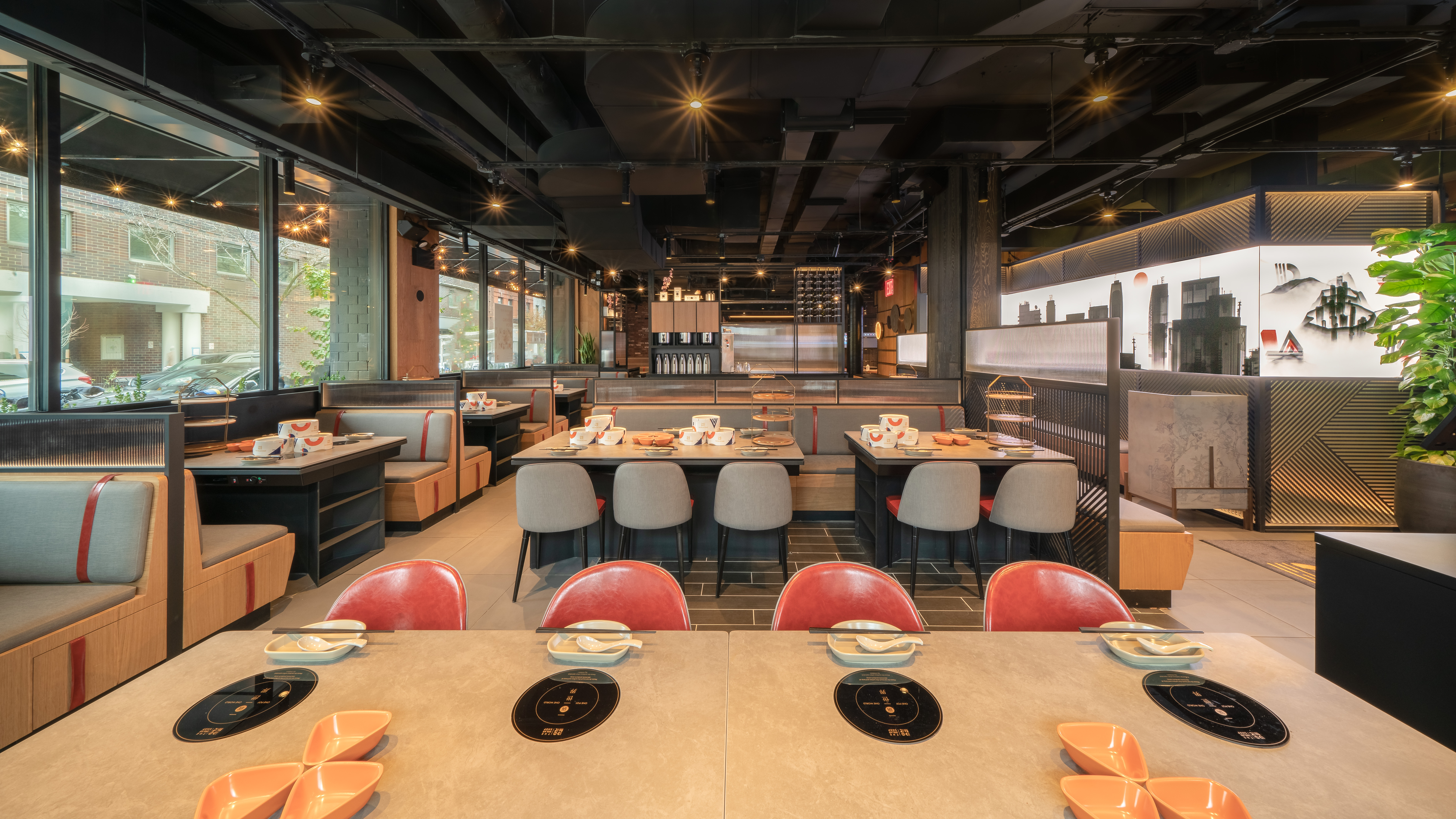 The interior of the hot pot restaurant the Dolar Shop with rows of large wooden tables and chairs
