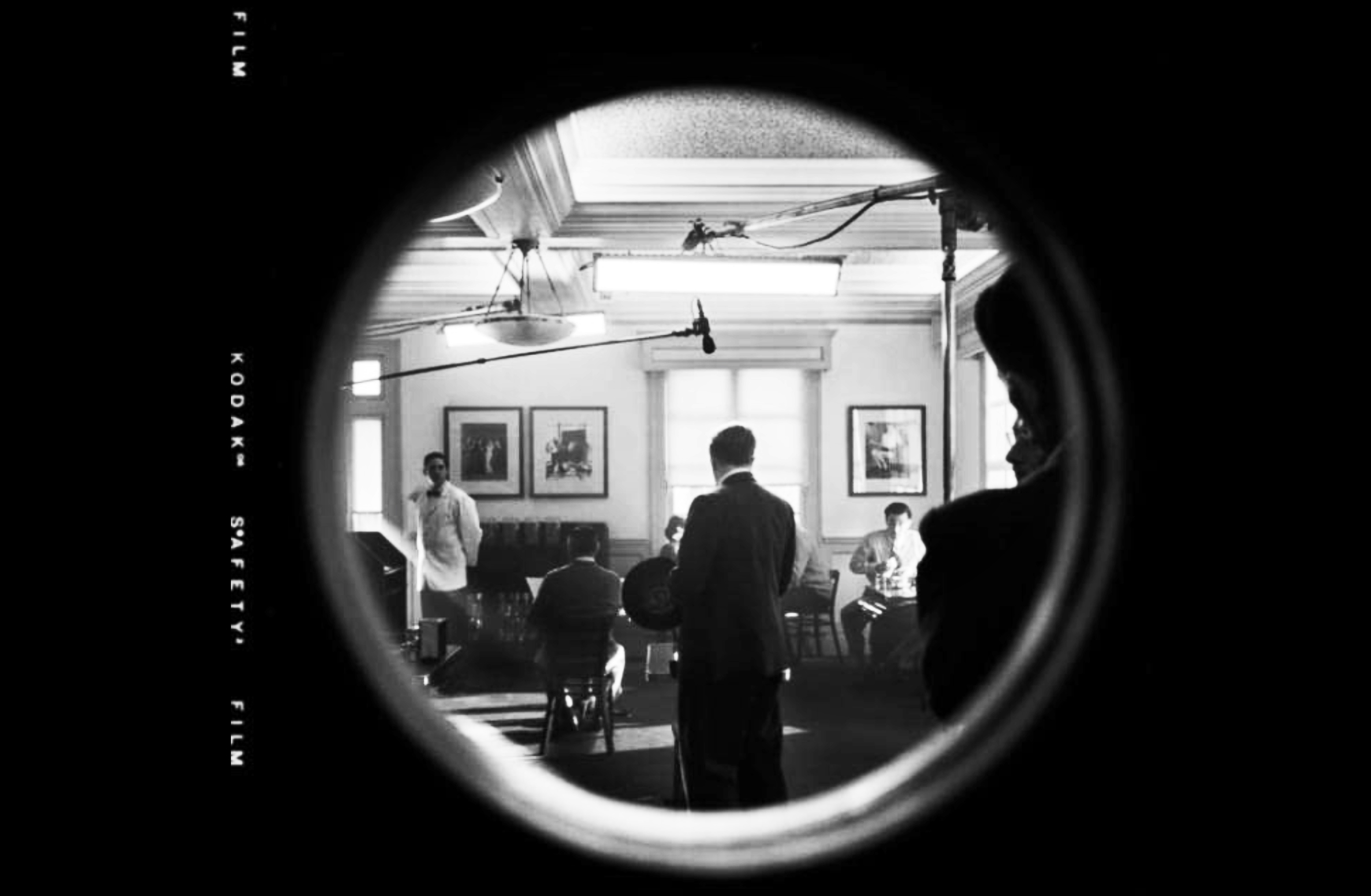The image looks through a round window into a room where a film is being shot.