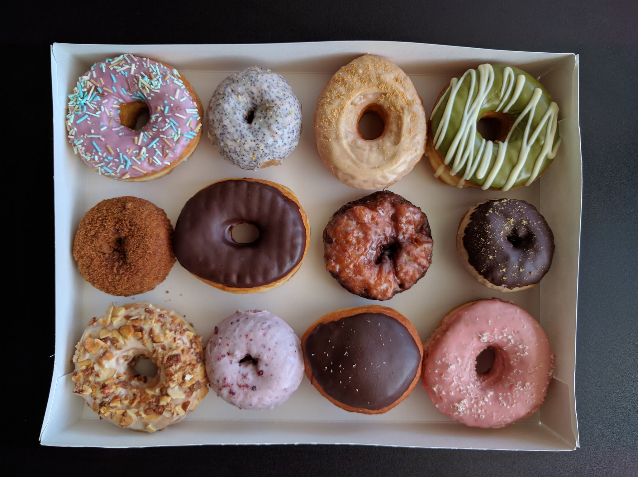 A box of Morningstar doughnuts covered in colorful glazes and sprinkles