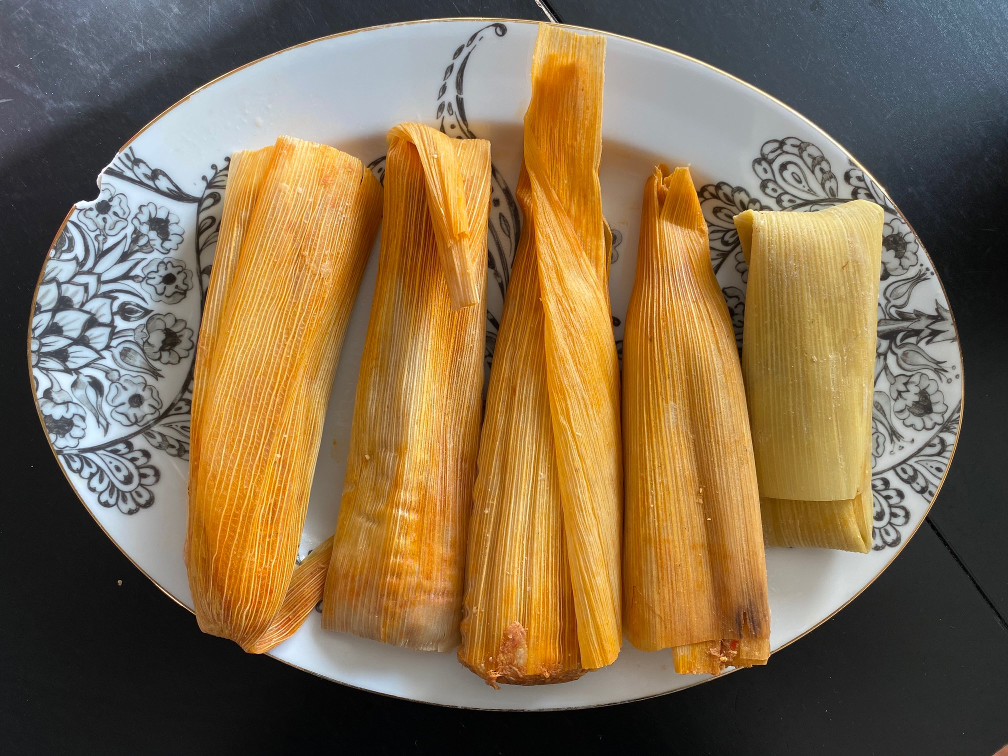 Five corn husk-wrapped tamales from Tamaleria Azteca on a ceramic platter
