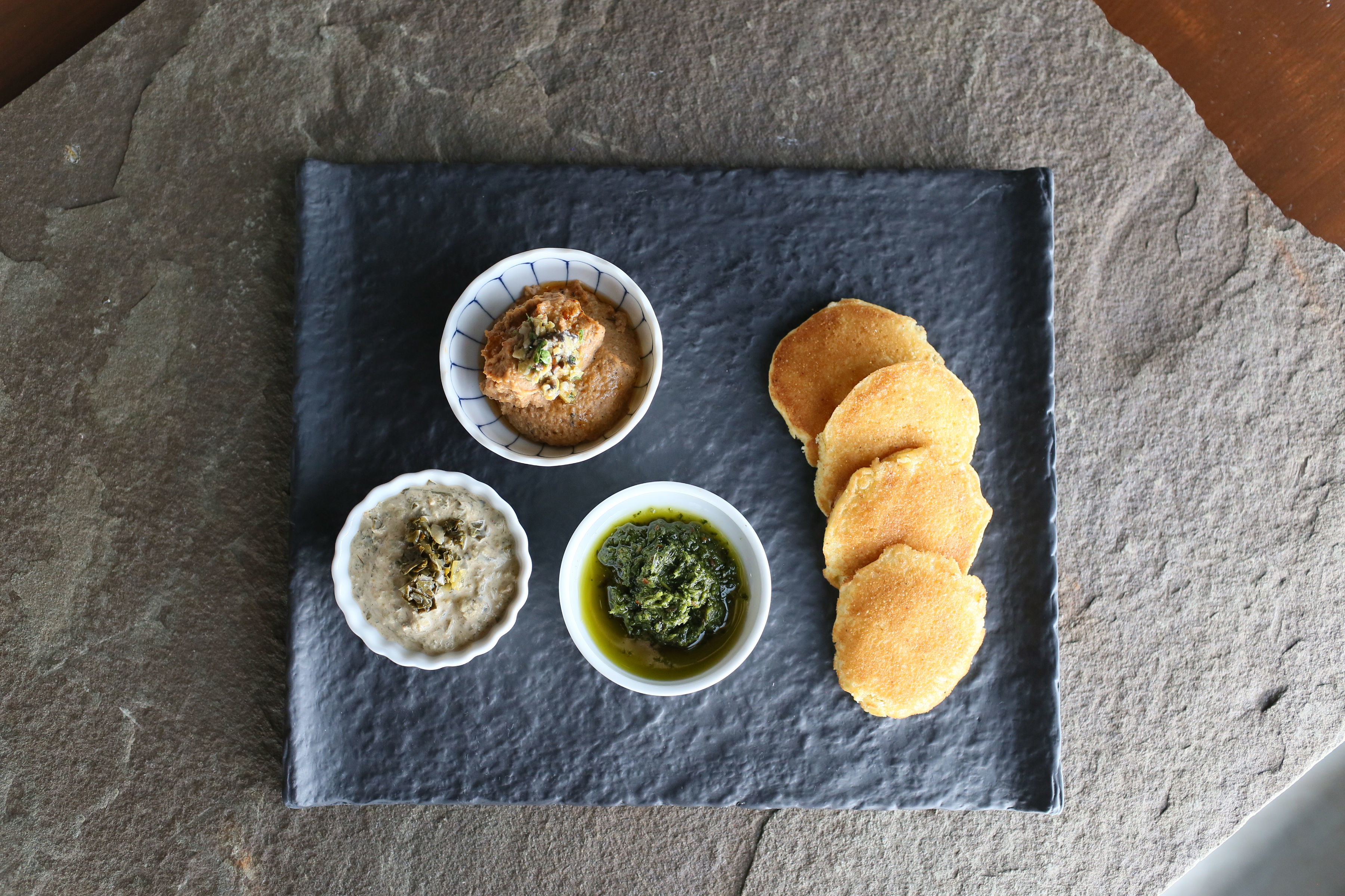 Black eyed pea hummus, roasted collard green dip, and zhug (a Yemenese hot sauce) on a plate next to four pieces of bread