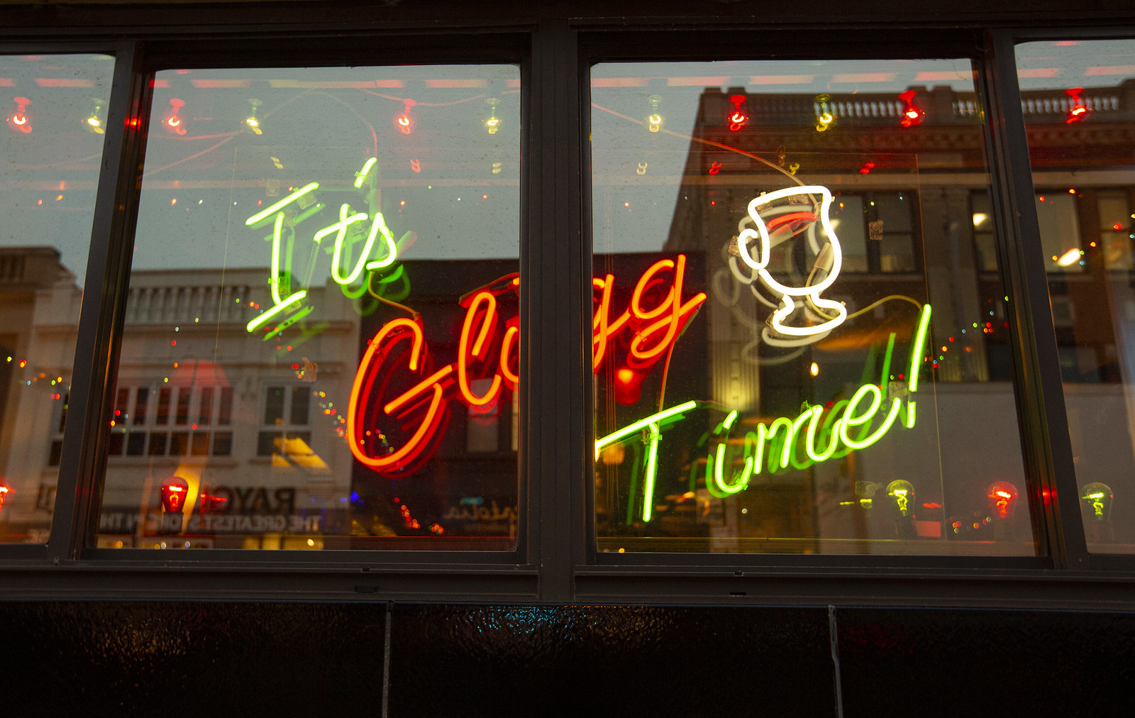 """A window with a neon sign reading """"It's glogg time."""""""