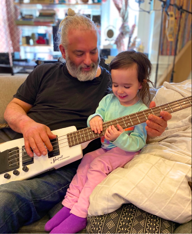 """Matthew """"Turk"""" Agostini playing guitar with his 3-year-old daughter Violet. He died in November from COVID-19."""