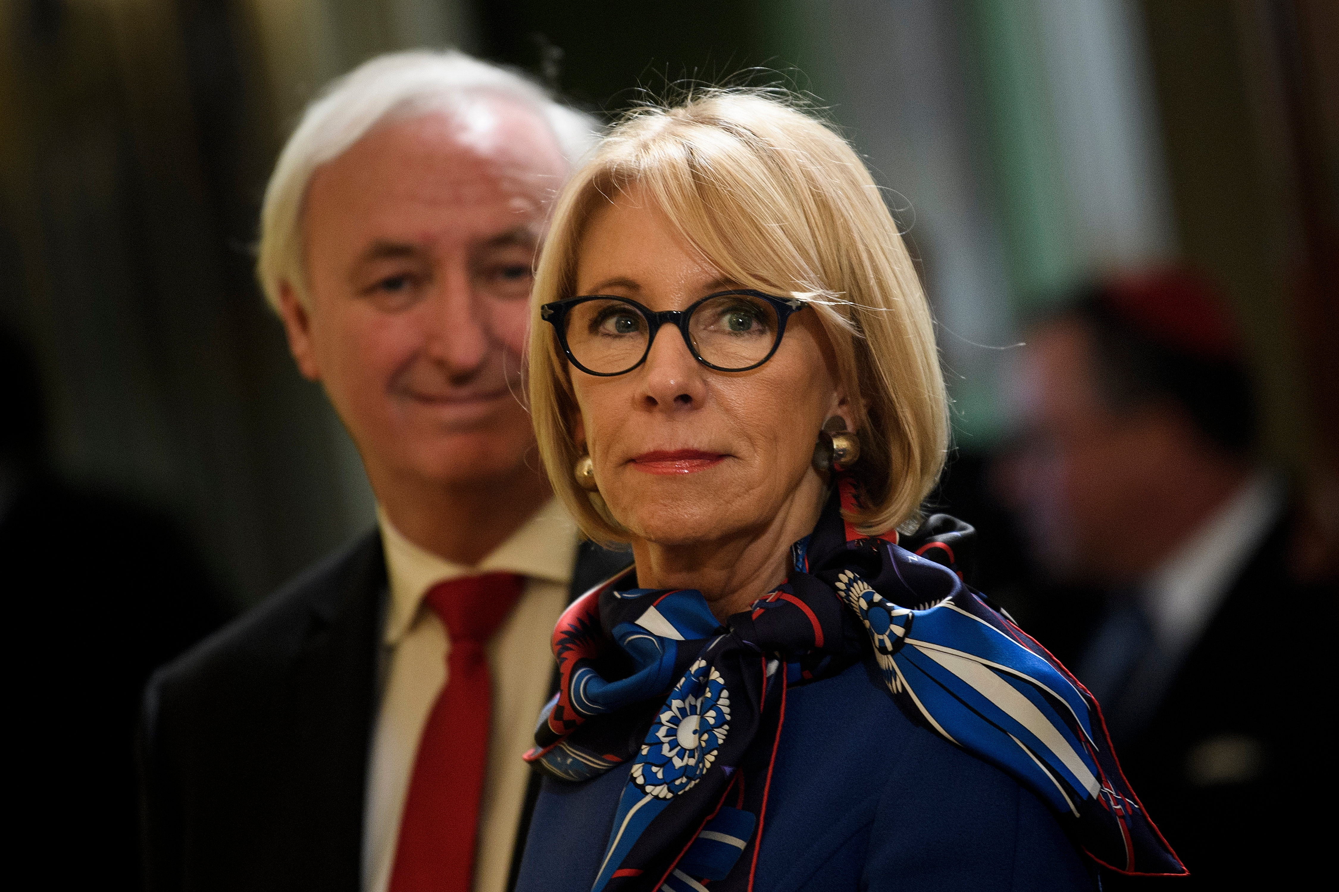 DeVos, in black rimmed square glasses, shoulder length blonde hair, a blue suit, and a blue, white, and red silk scarf, smiles slightly. A blurry crowd is behind her.