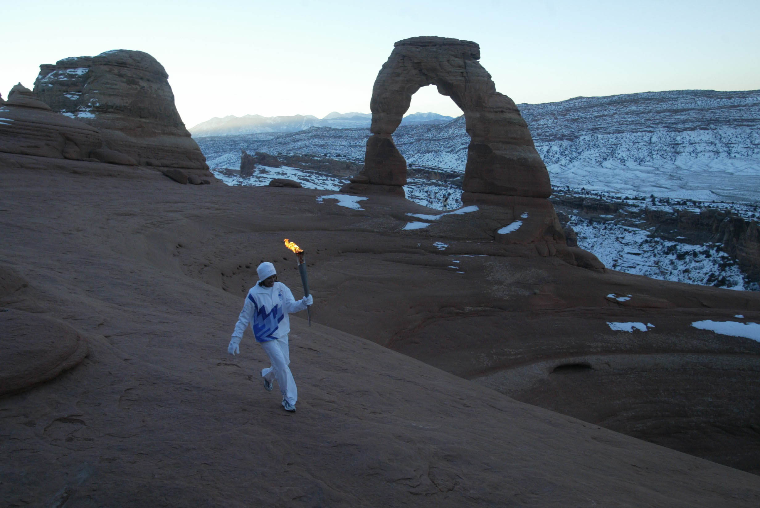 Native American Stephanie Laree Spann walks the Olympic Torch past Delicate Arch in Arches National Park, near Moab, Utah on Feb. 2, 2002.