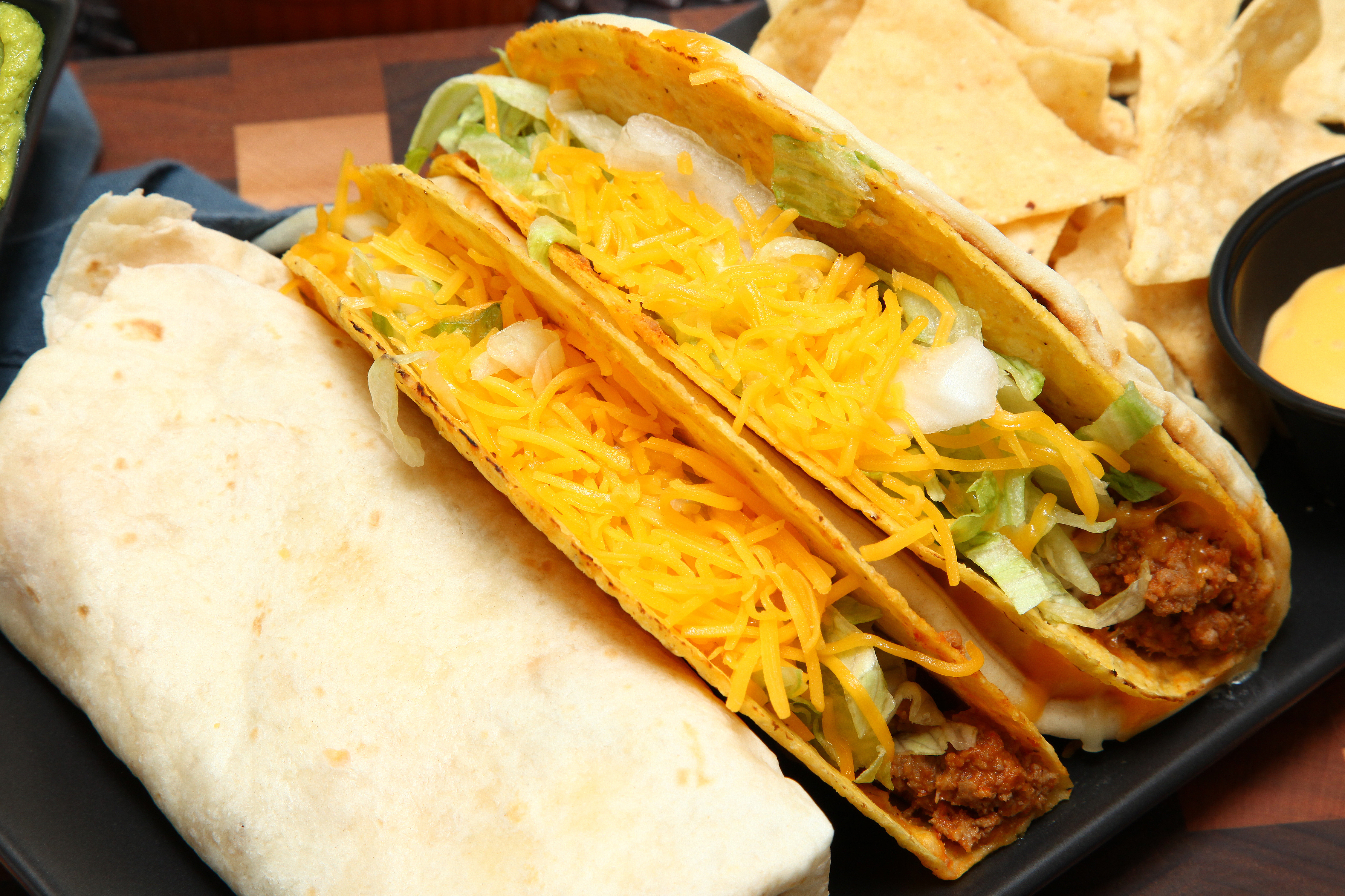 A burrito and two tacos covered in shredded cheese