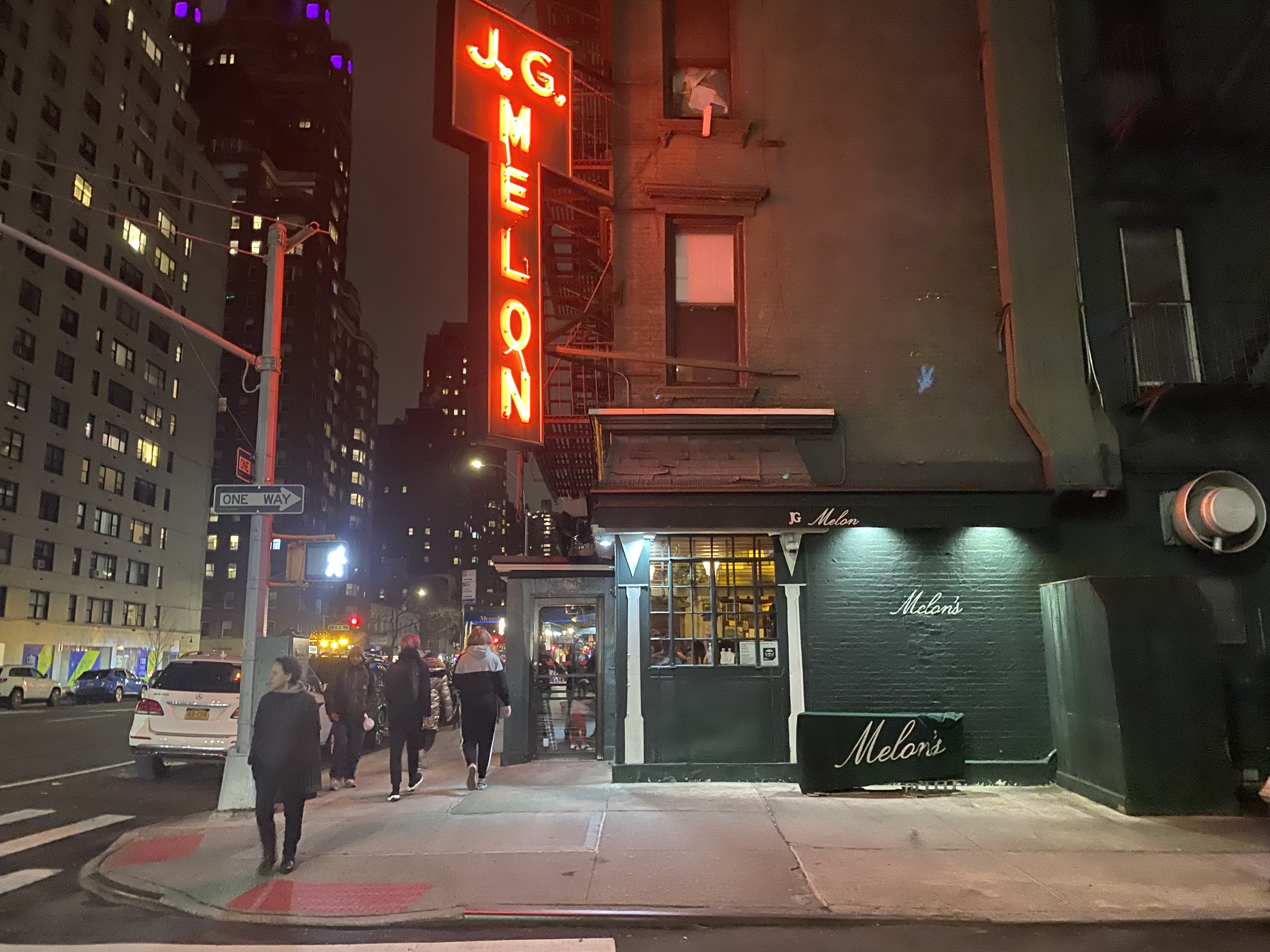 A neon red awning hangs upright outside of J.G. Melon, beckoning patrons inside