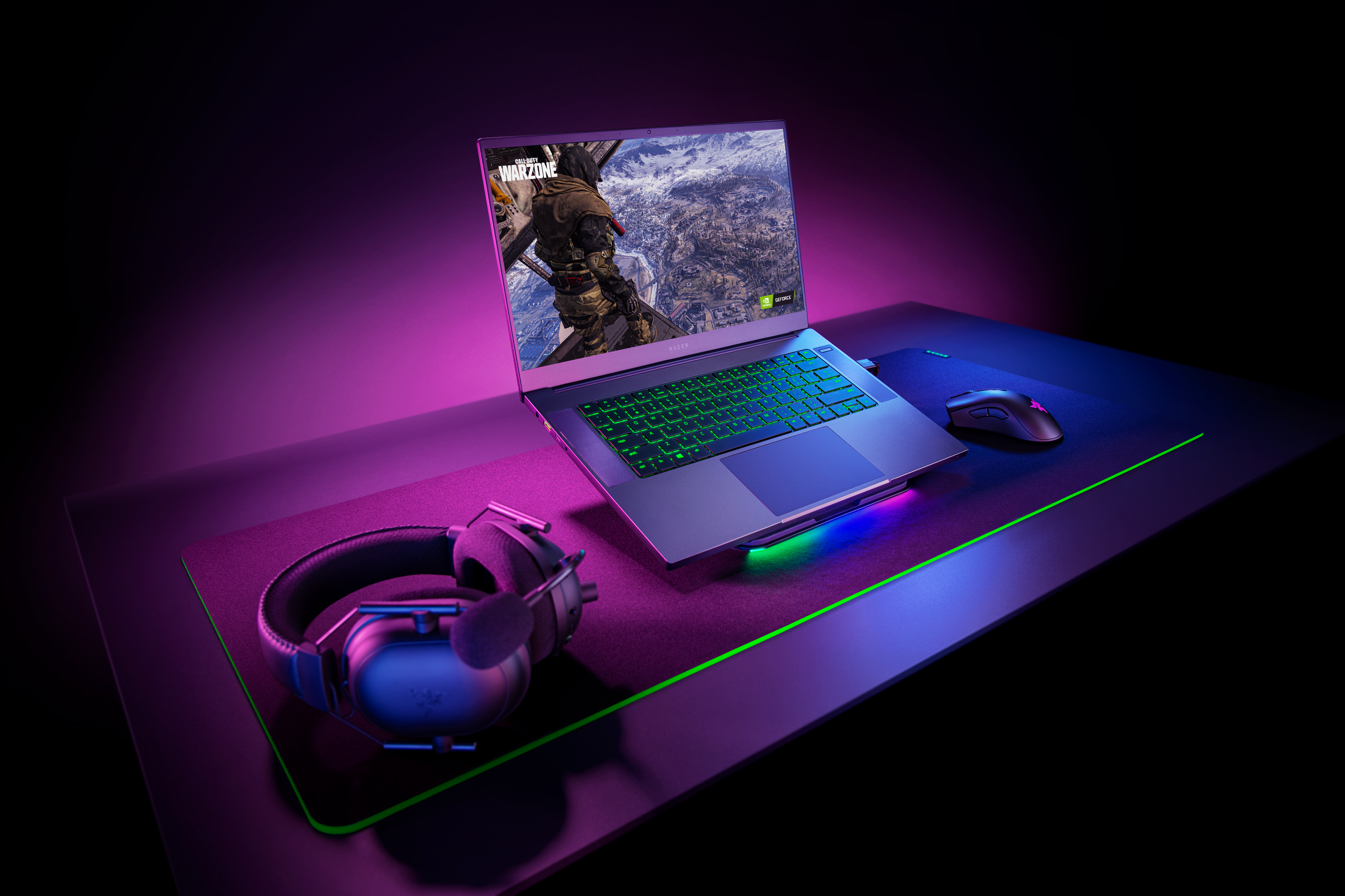 The Razer Blade 15 Base sits on a stand on a table with a pair of headphones and a mouse.