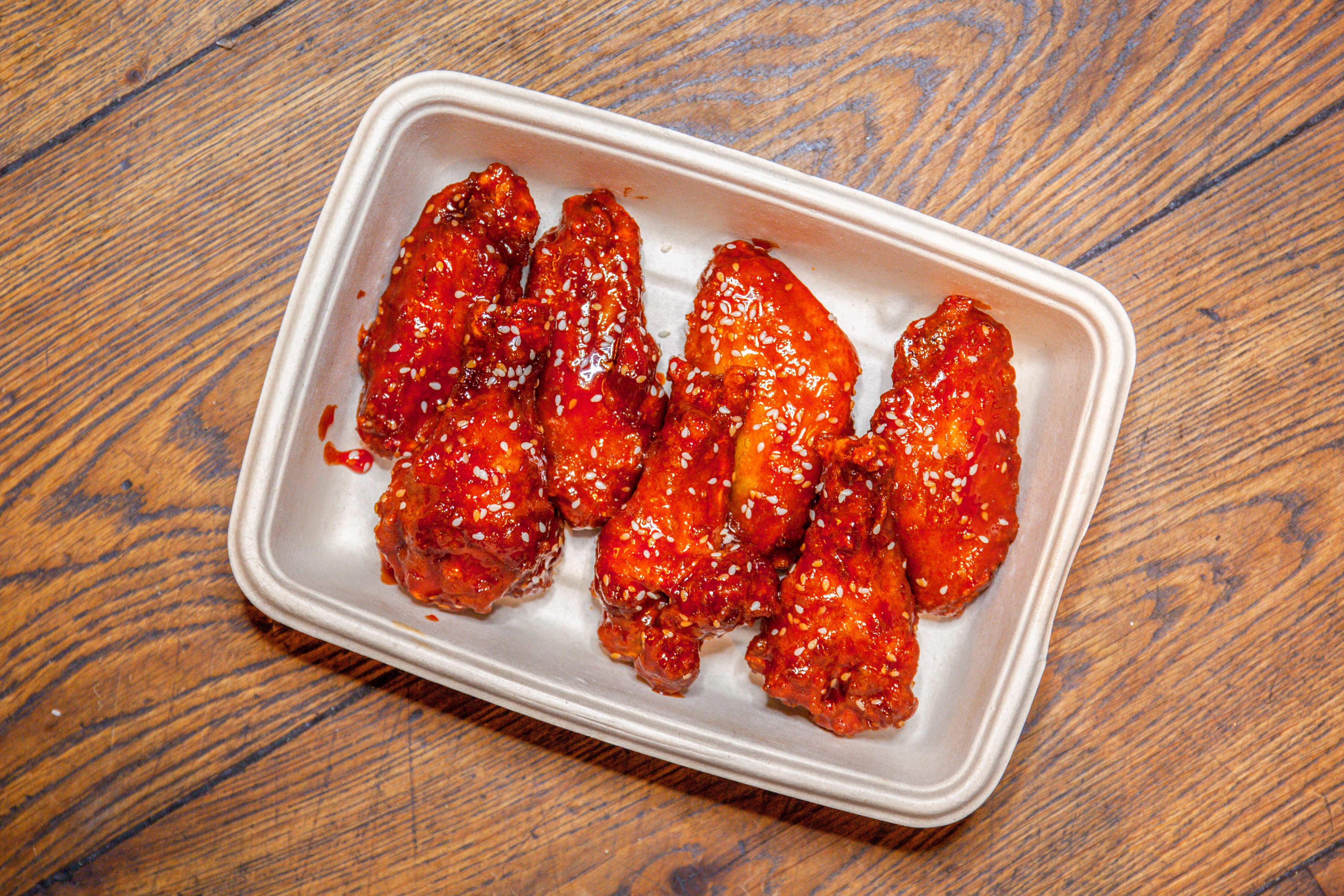 Twice-fried Korean chicken wings with a chili glaze and sesame seeds($18)