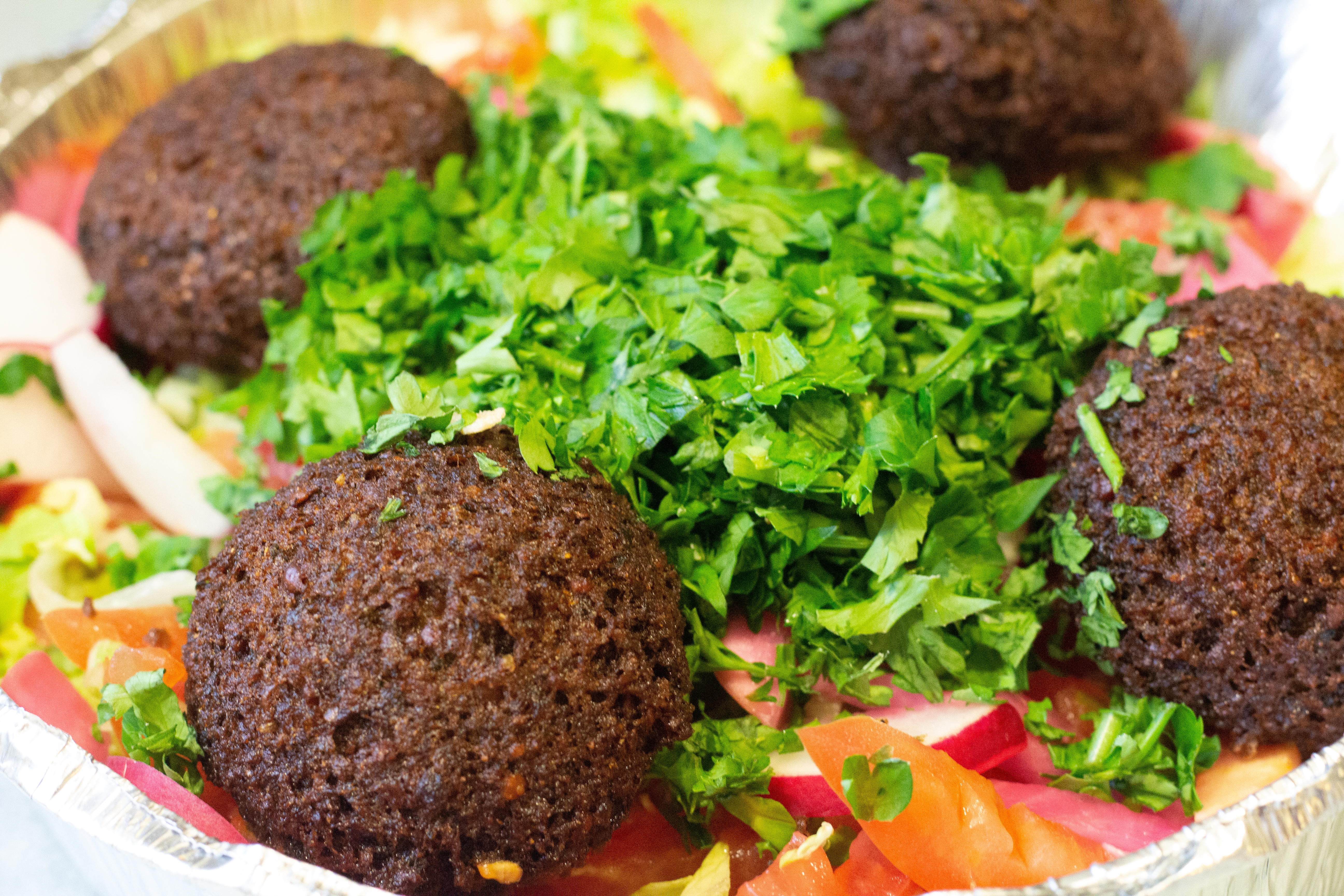 Four golden brown falafel pieces sit in a takeout container with a massive pile of chopped parsley in the center