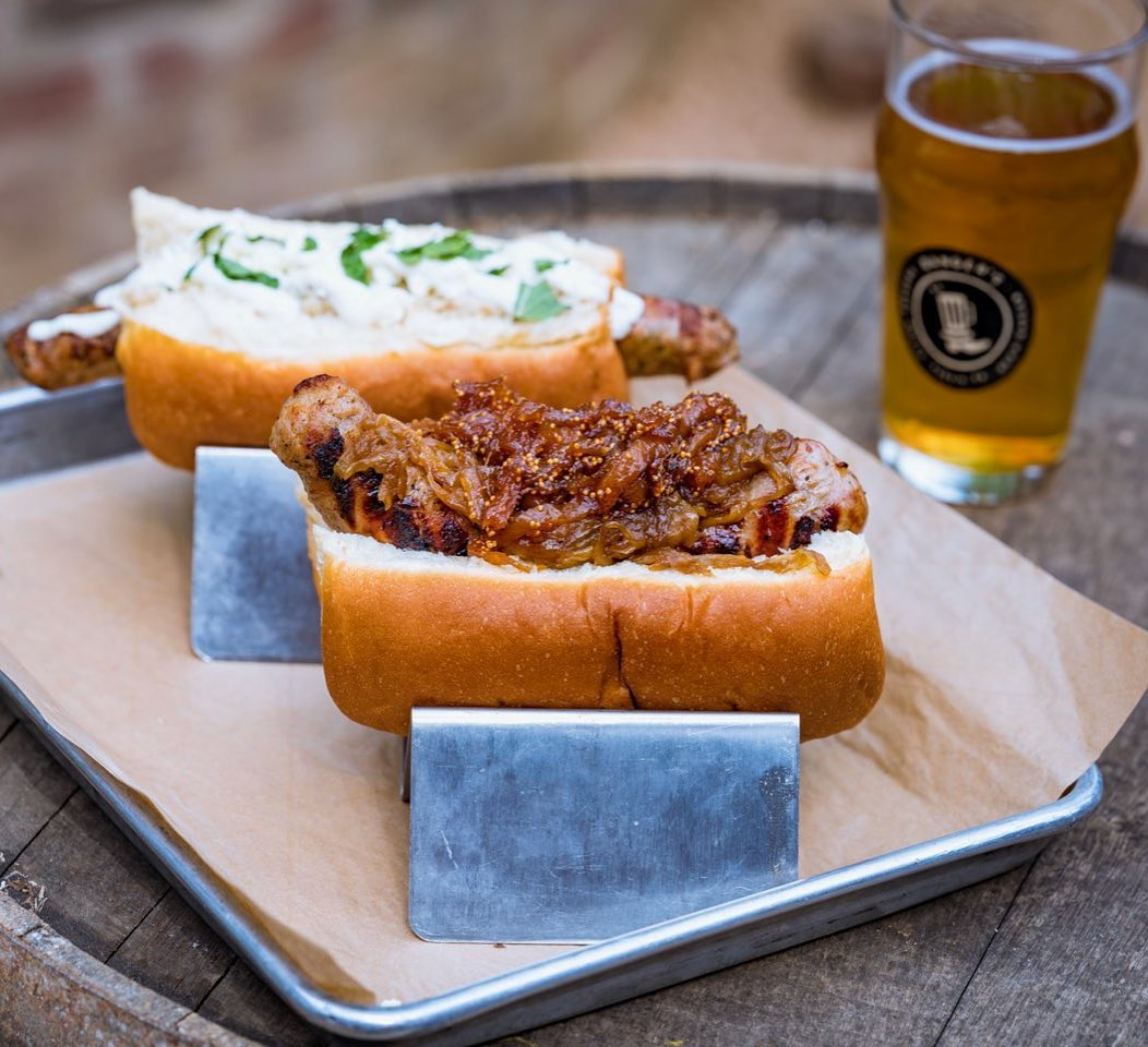 in front, a bun with barely visible sausage covered in caramelized onion, in back, bun with sausage, both in metal holders on a paper-lined tray, with a beer on the right