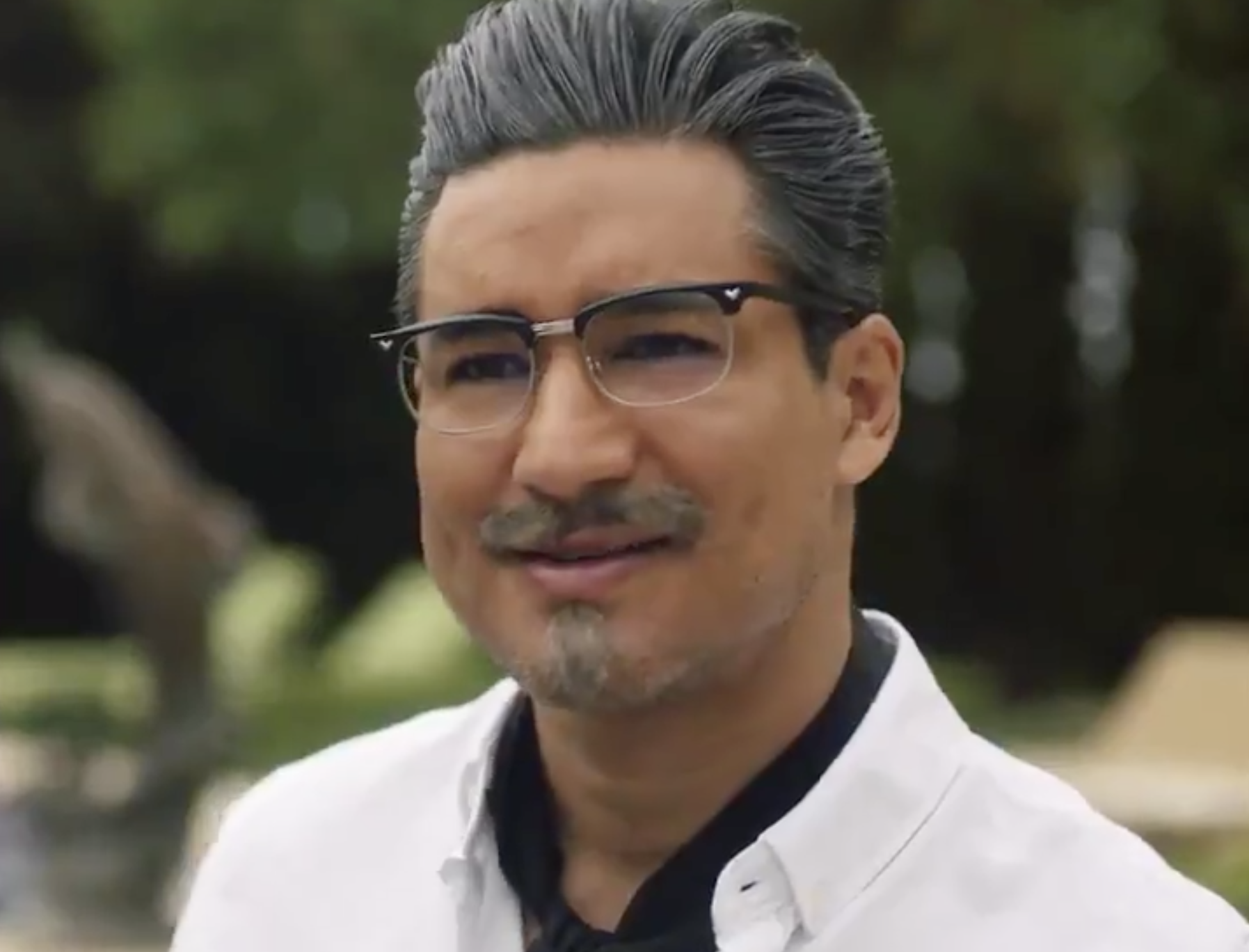 A handsome latino man with gray slicked back hair and a goatee stands outside a large estate dressed in a white shirt, black ascot, and black framed glasses.