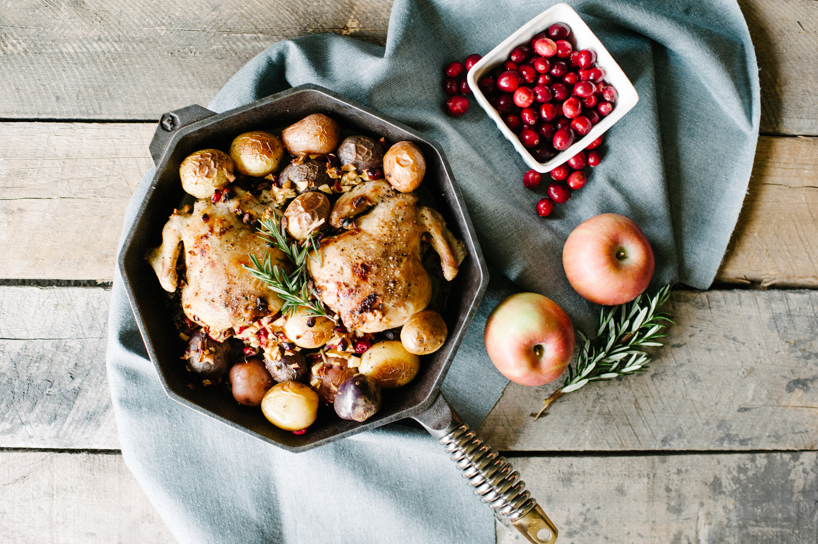 Two Cornish game hens sit snugly in a Finex skillet with potatoes on a table