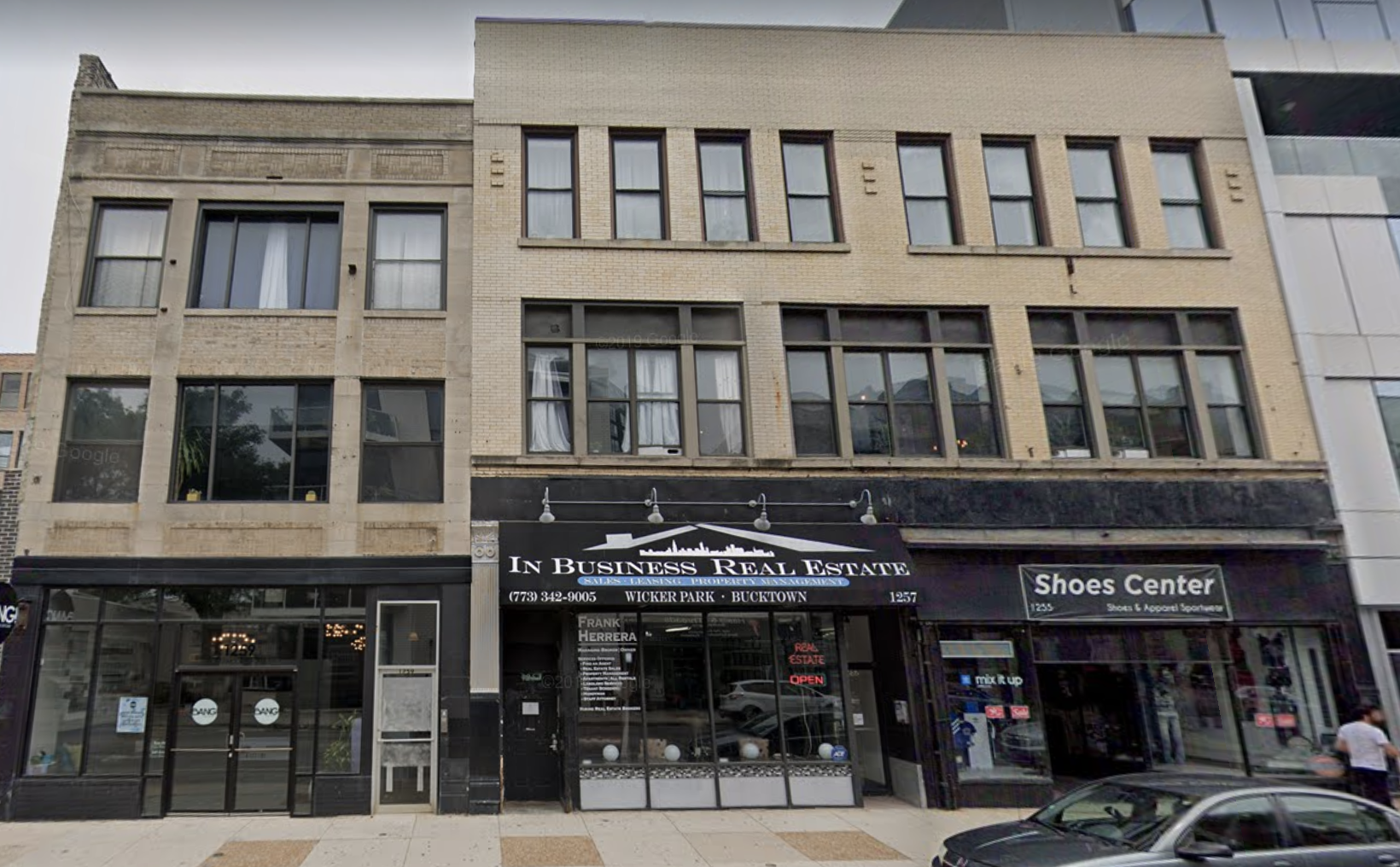 """A three-story building in Wicker Park. Black awning on the front reads """"In Business Real Estate."""""""