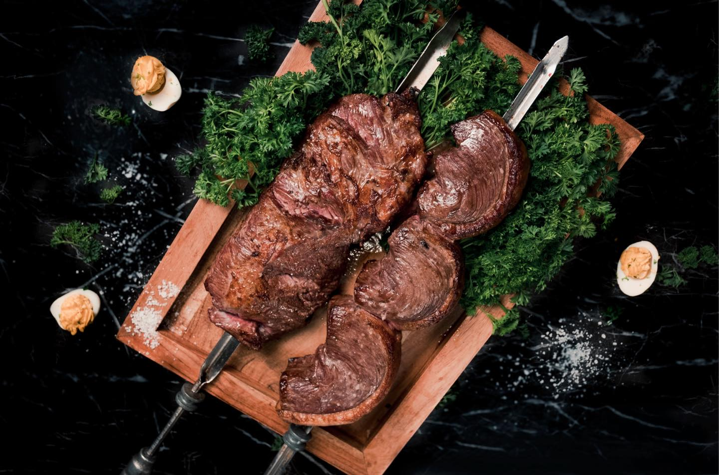 Meat on two skewers on a cutting board