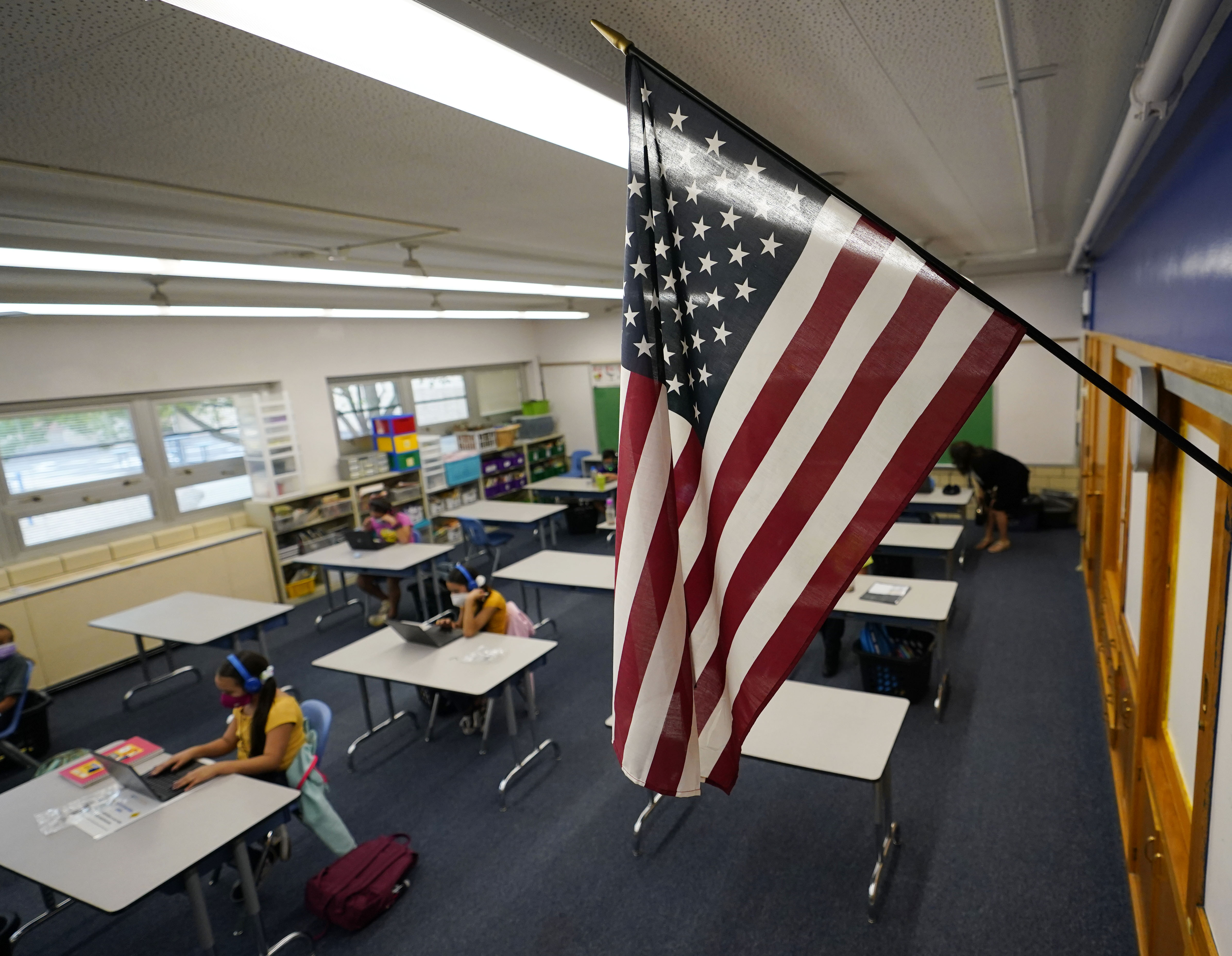 An American flag hangs over a classroom full of masked students working at desks.
